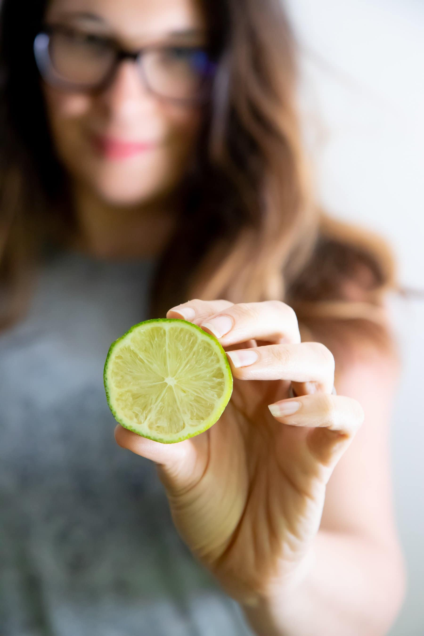 Woman holding out a halved lime, cut side towards the camer