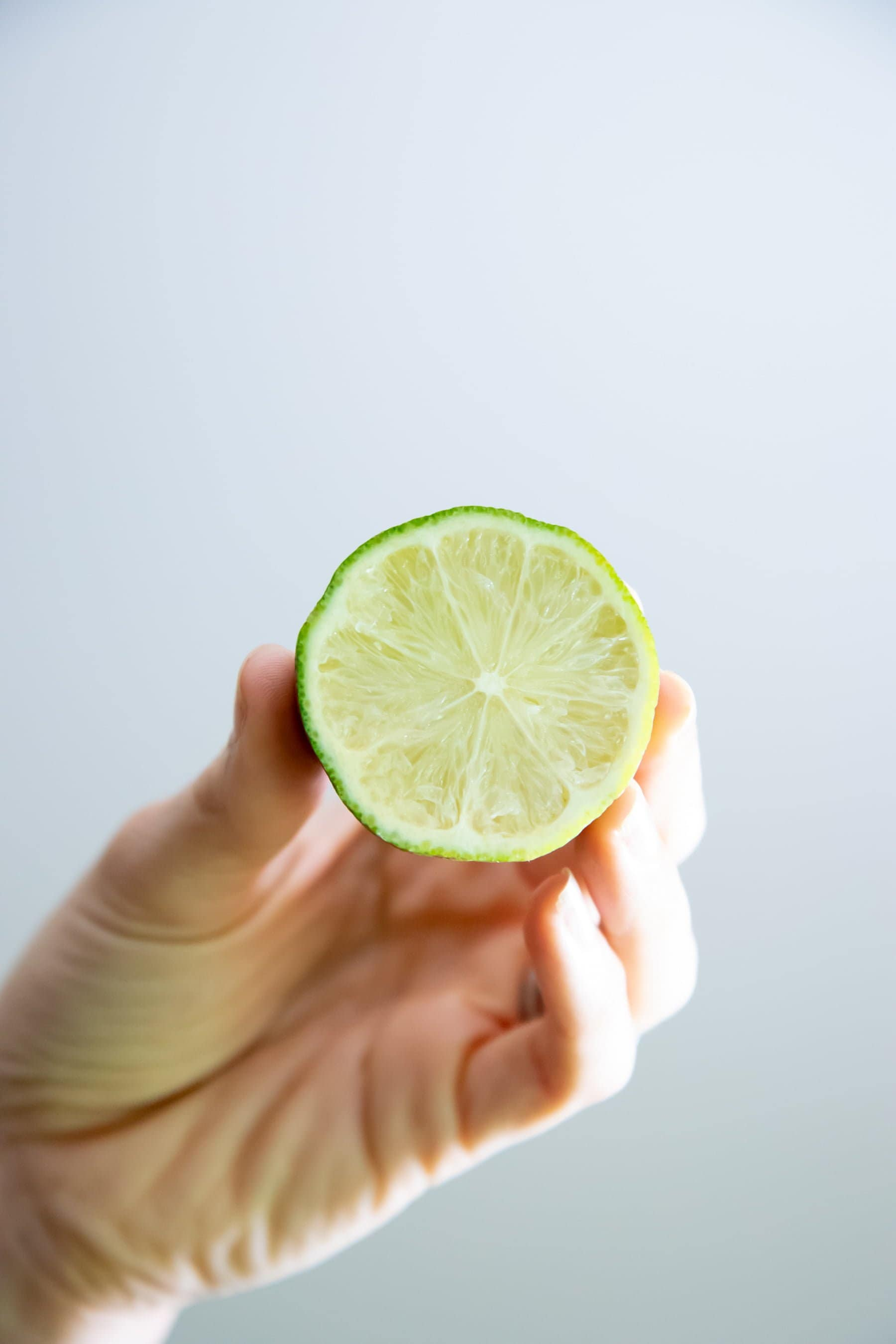 Hand holding a halved lime, with the cut side facing the camera