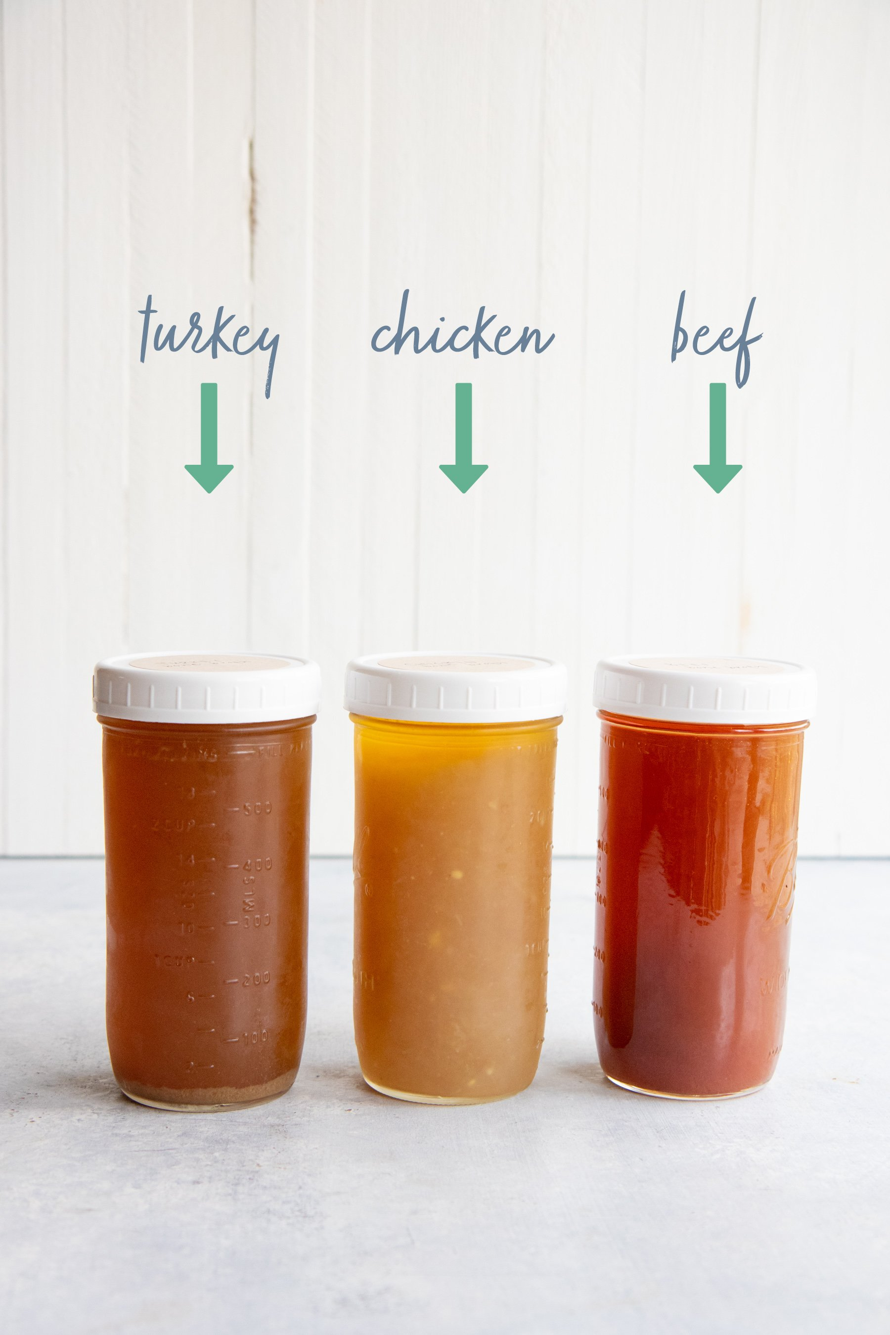 Side shot of three jars of bone broth - made from turkey, chicken, and beef bones