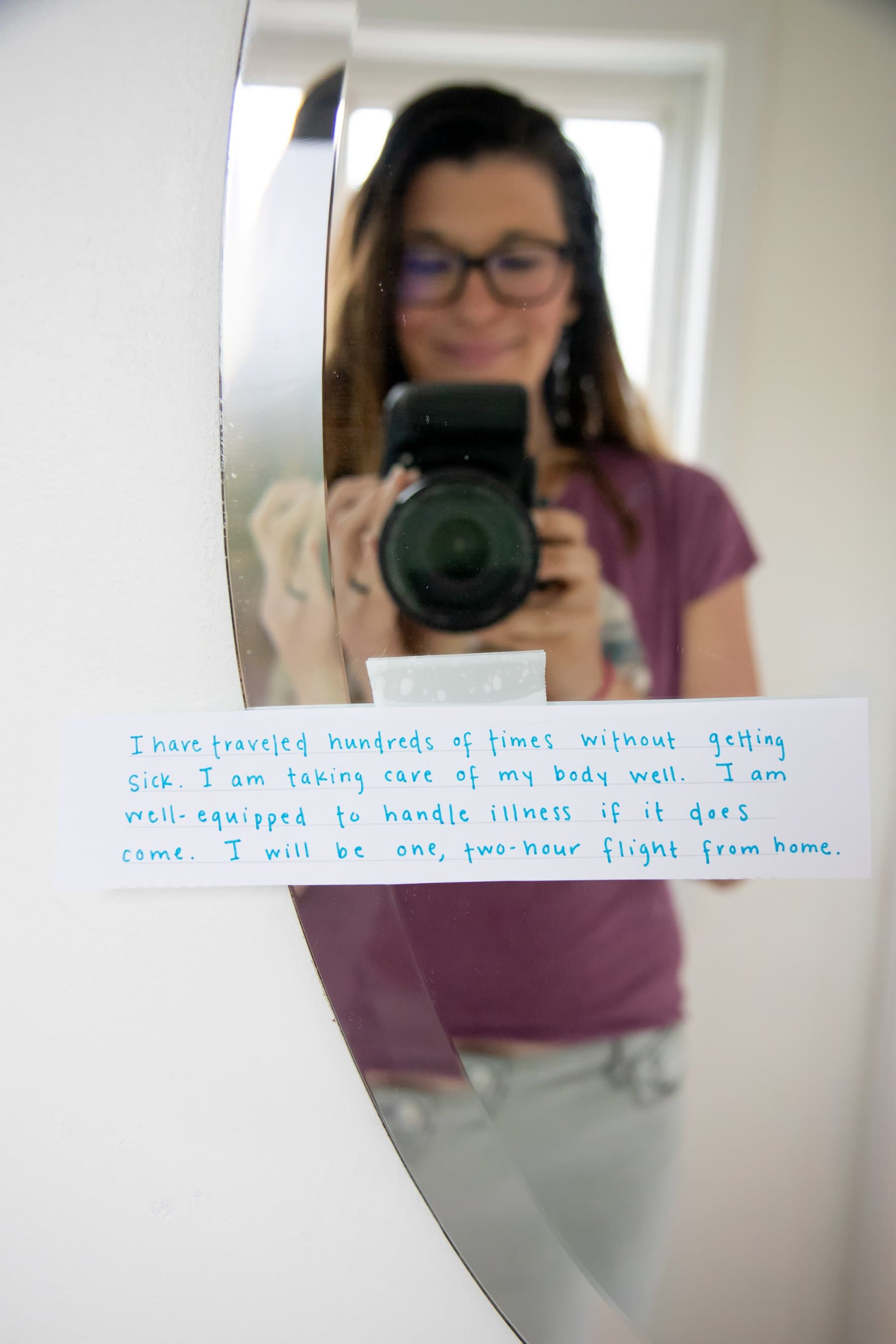 Shot of a Worry Time hot thought taped to a mirror, with a woman holding a camera in the reflection