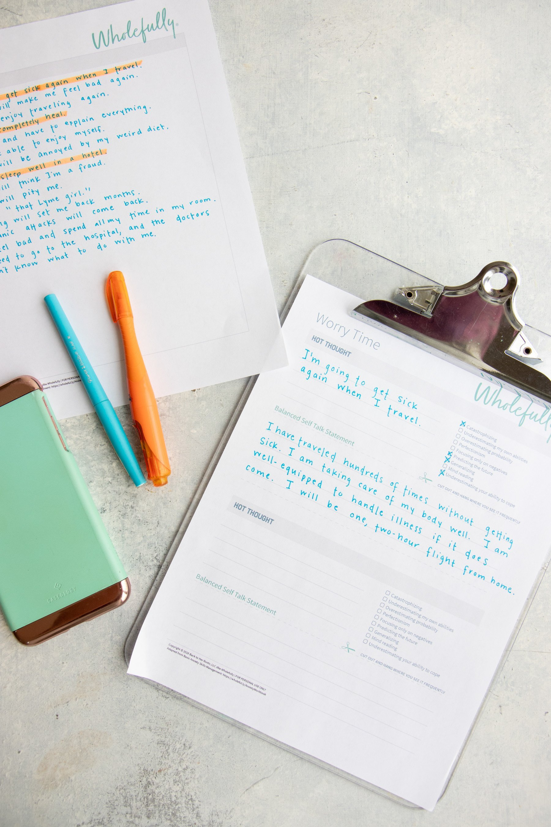 Overhead shot of a clipboard, pen, highlighter, phone, and printable Worry Time worksheets
