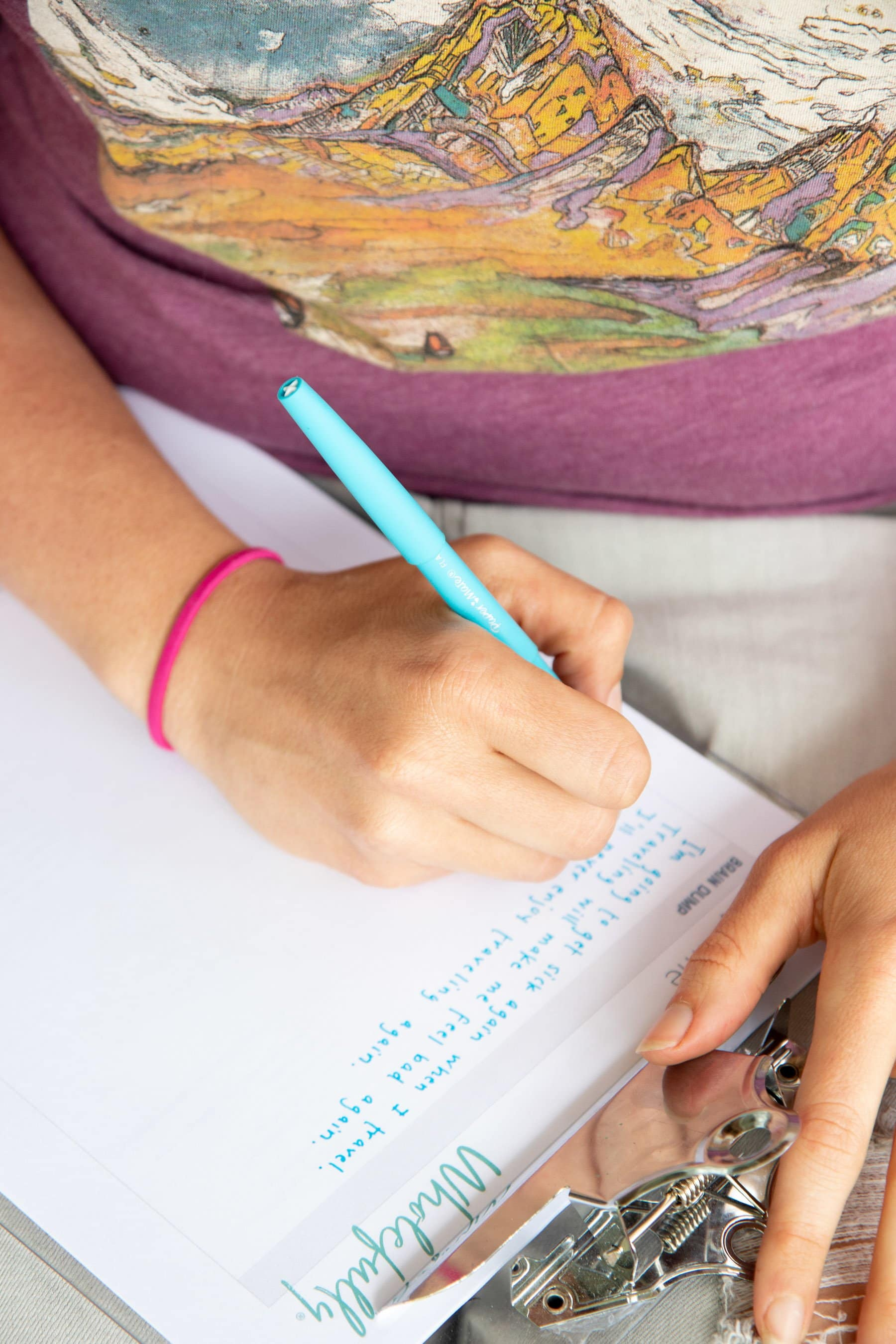 Overhead shot of a hand writing with a blue pen on a clipboard to fill in a Worry Time worksheet