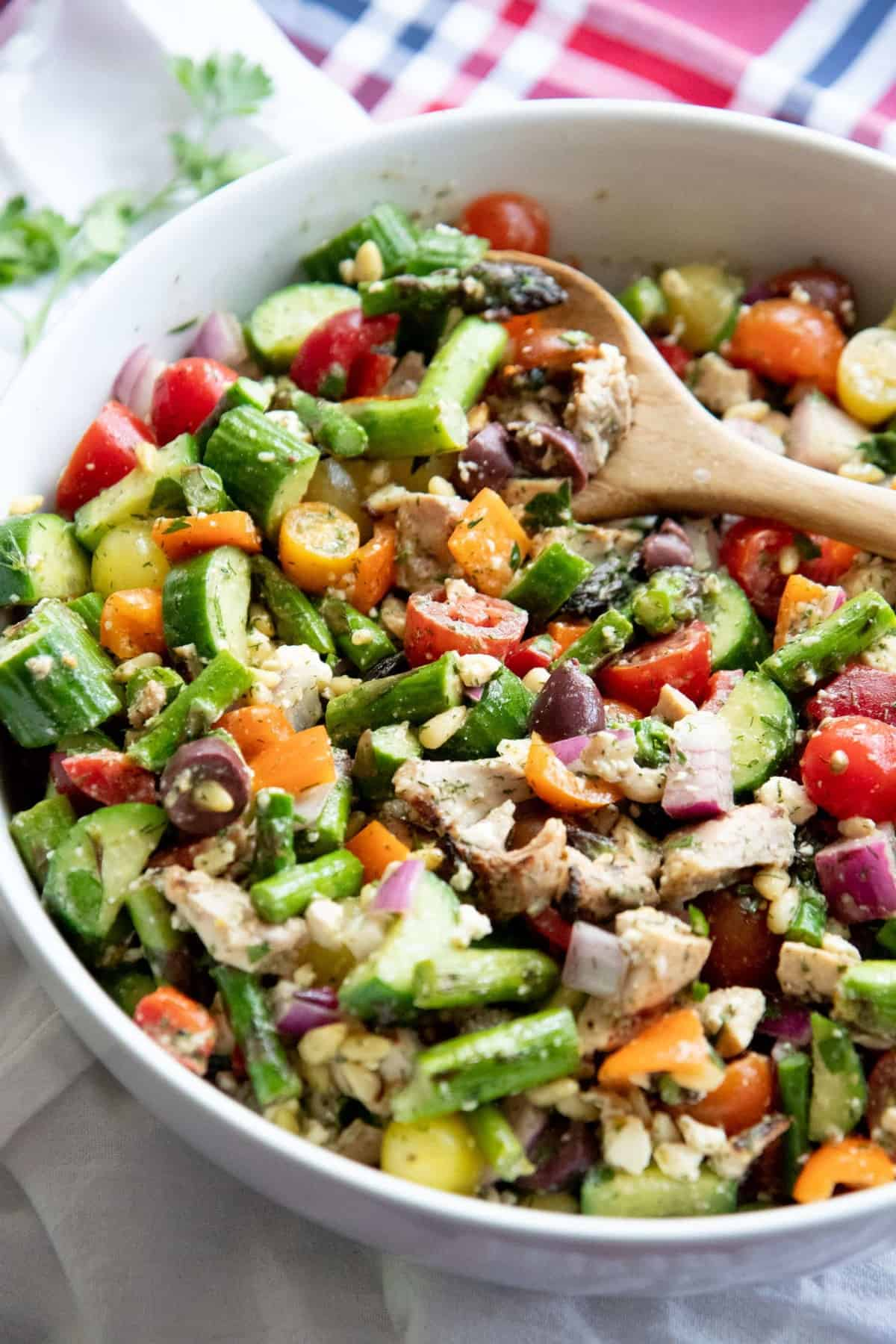 Side angle shot of Grilled Chicken and Asparagus Chopped Greek Salad in a white bowl