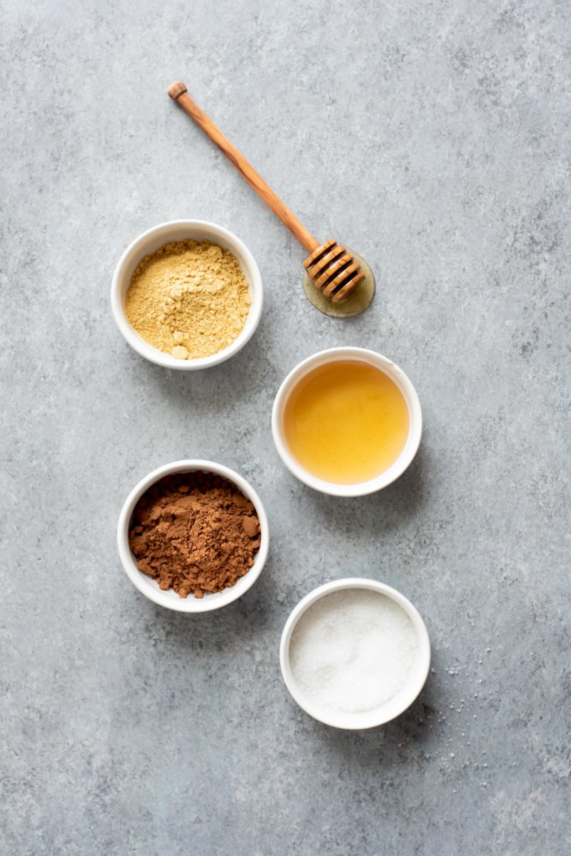 Overhead shot of ingredients for Ginger Bites (an all-natural upset stomach remedy) on a gray surface