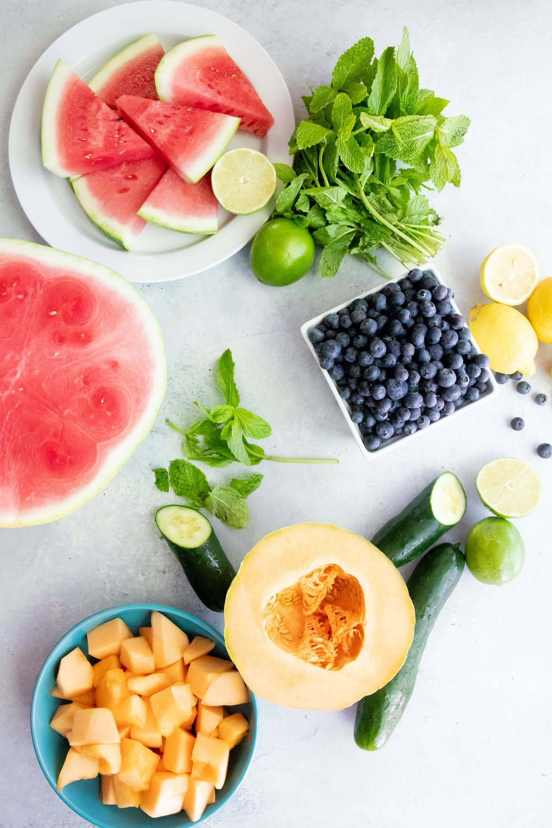 Ingredients for Frozen Fruit Pops arranged on a white background -- watermelon, cantaloupe, cucumber, blueberries, lemons, and limes