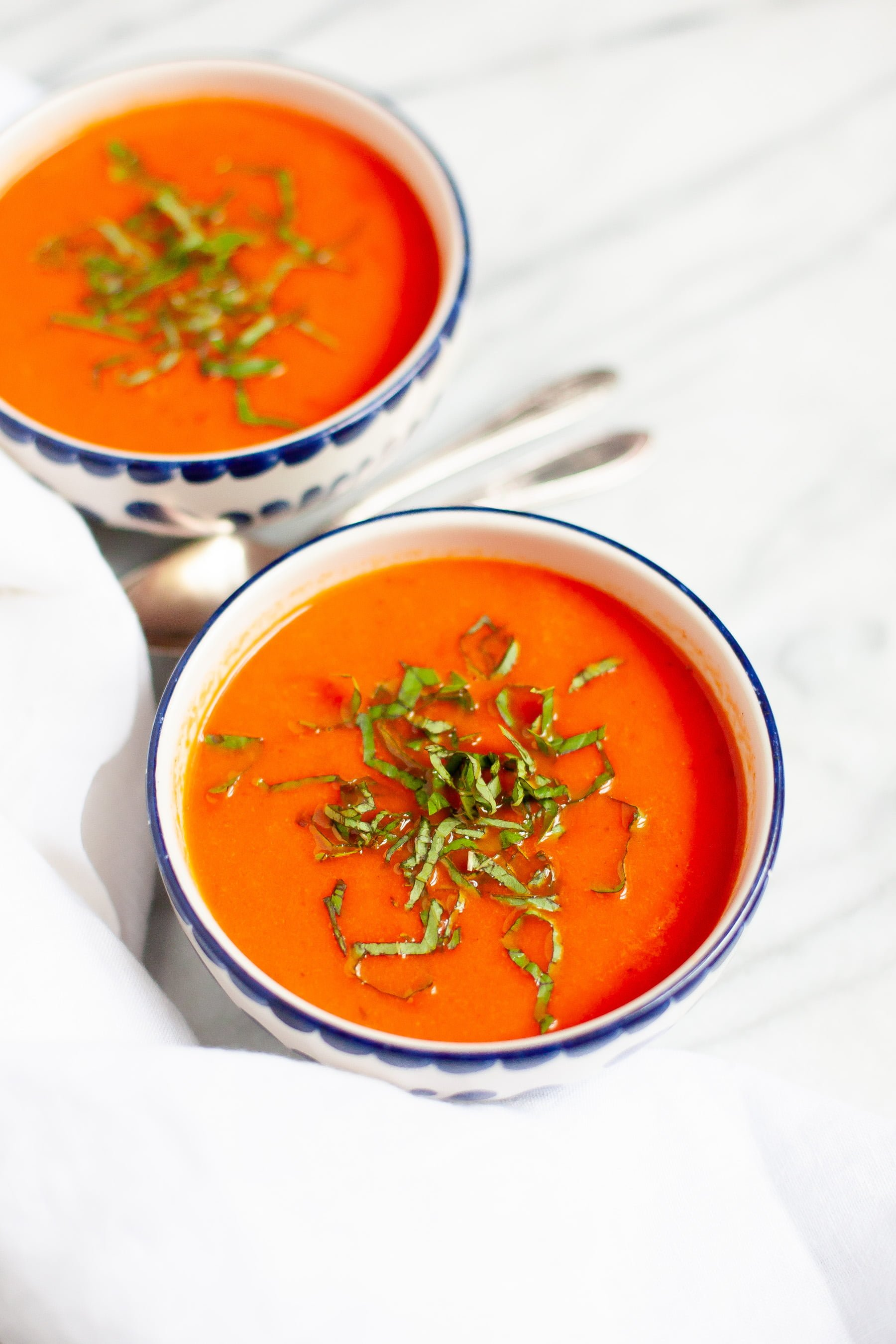 Single angle shot of Garden Fresh Tomato Soup on a white background, with whole tomatoes off to the side