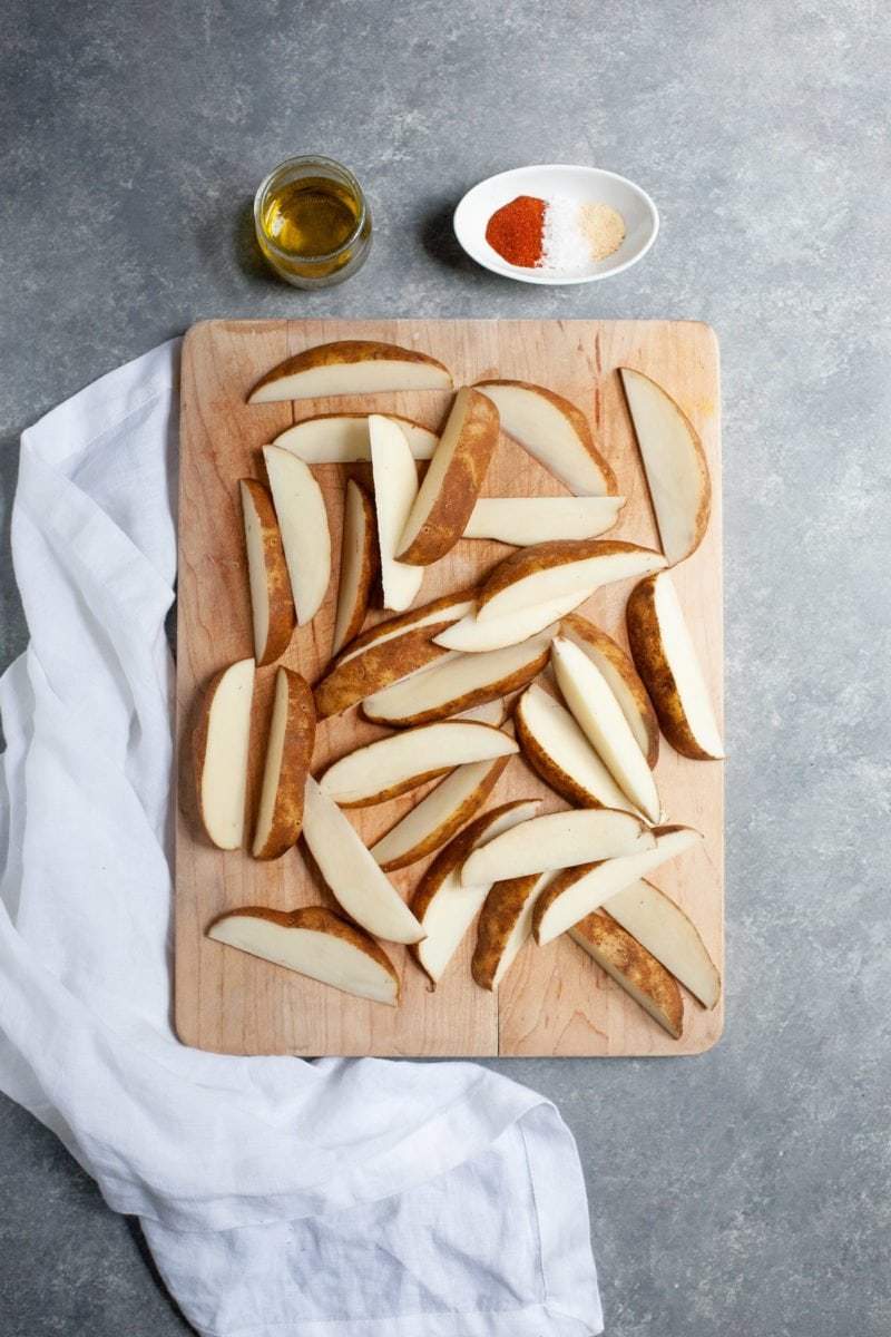 Overhead shot of potatoes cut into wedges on a wooden cutting board