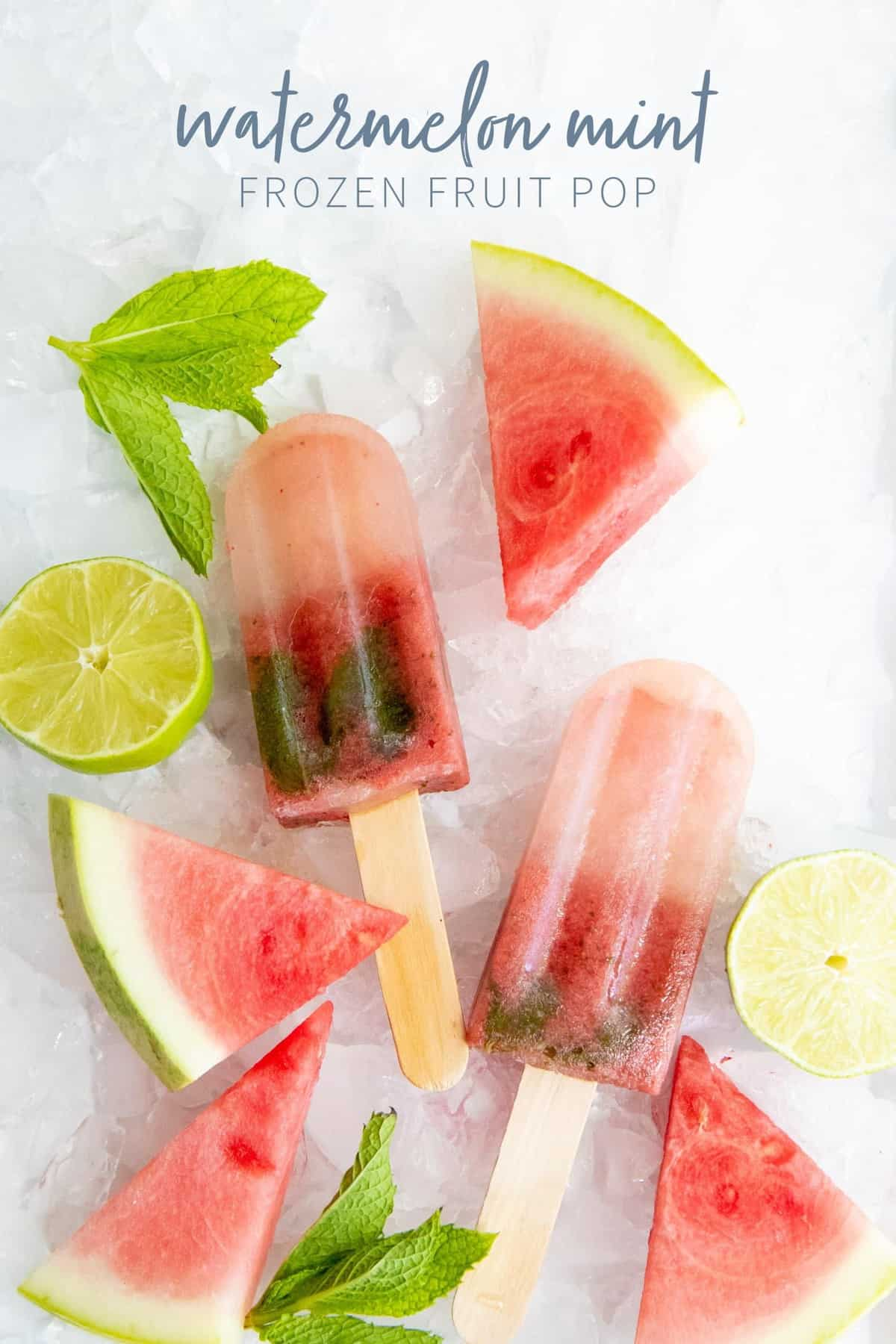 Watermelon Mint Frozen Fruit Pops on a bed of crushed ice, surrounded by watermelon wedges, mint sprigs, and half a lime