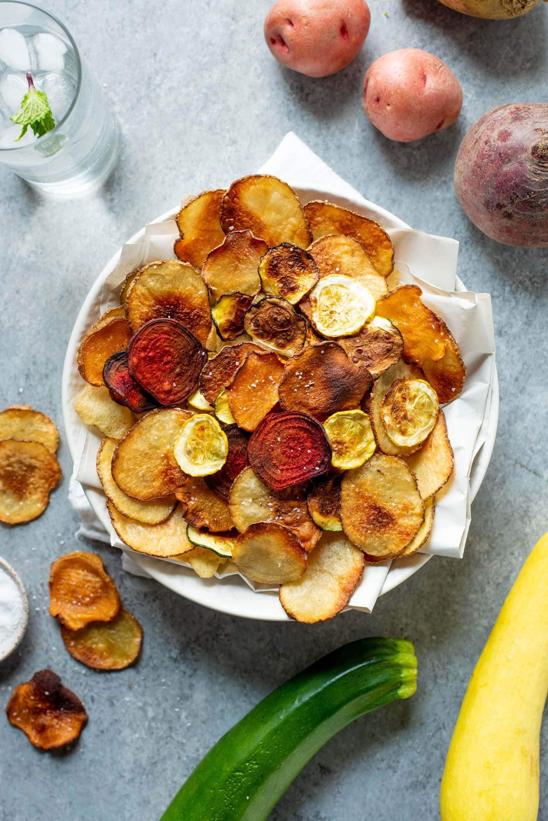 Overhead shot of Baked Vegetable Chips in a white bowl, surrounded by whole veggies