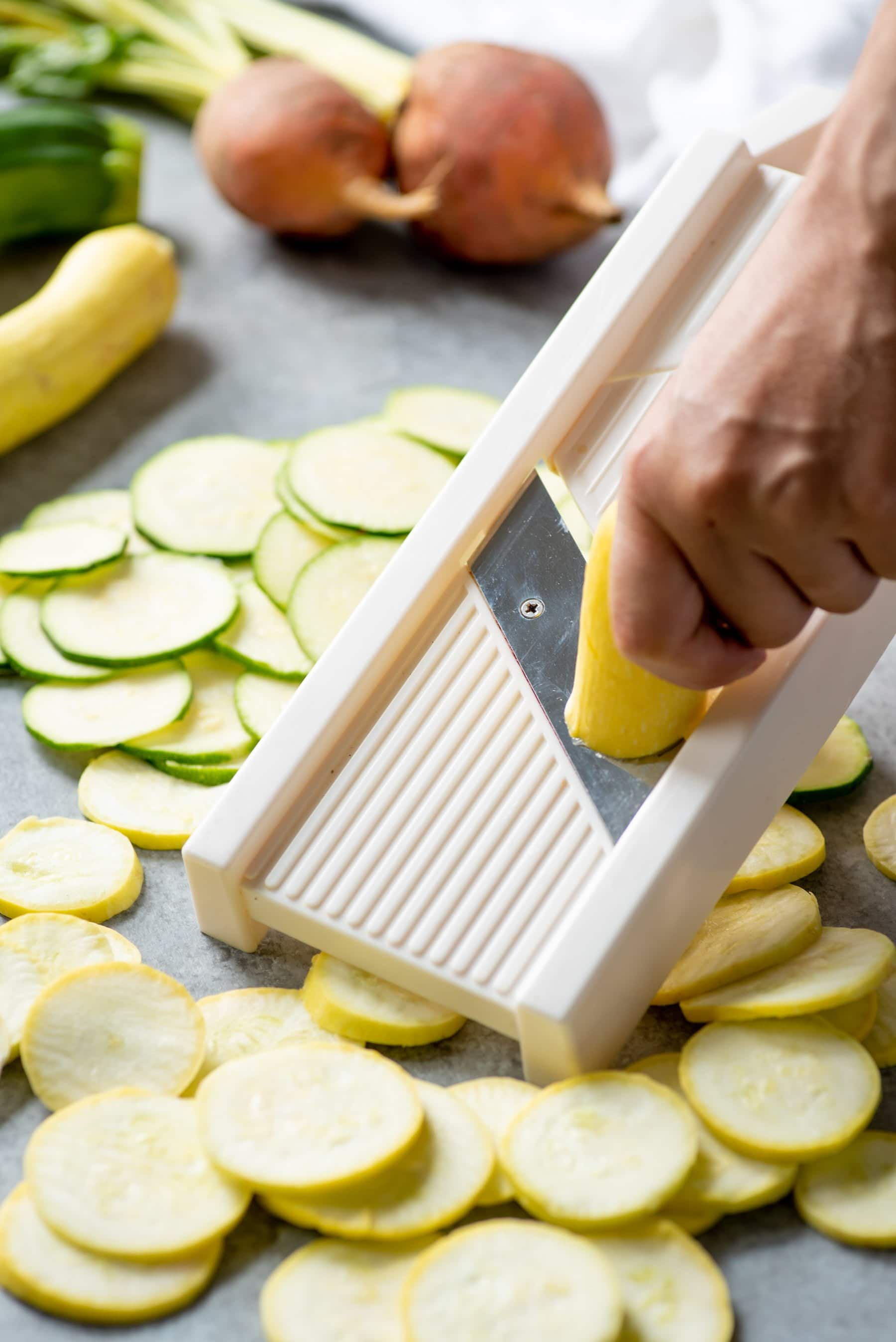 Hand slicing yellow squash and zucchini on a mandoline slicer