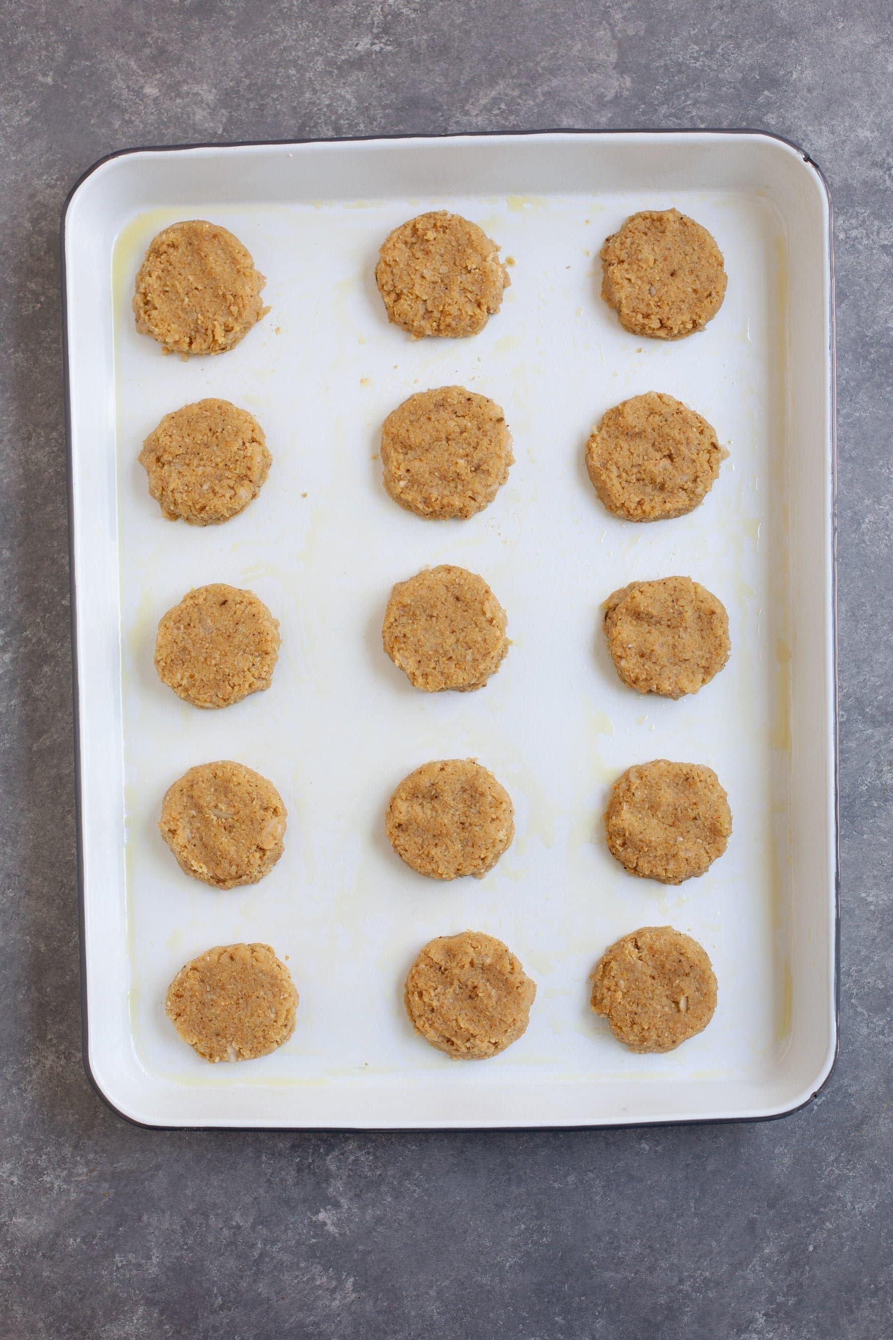 Falafel patties lined up on a baking dish, ready for cooking