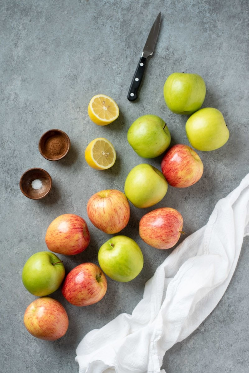 Green and red apples on a grey background, with a halved lemon and some spices