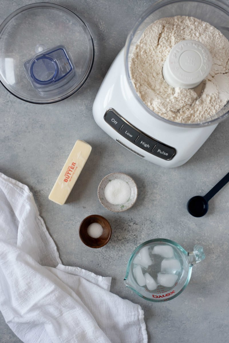 Ingredients for a perfect pie crust around a small food processor