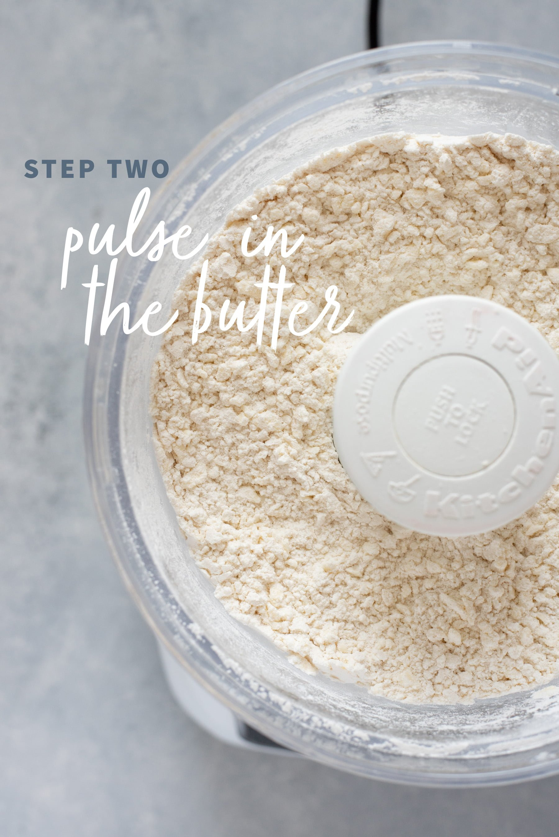 Pulsing butter into the dry ingredients for pie crust dough in the bowl of a food processor