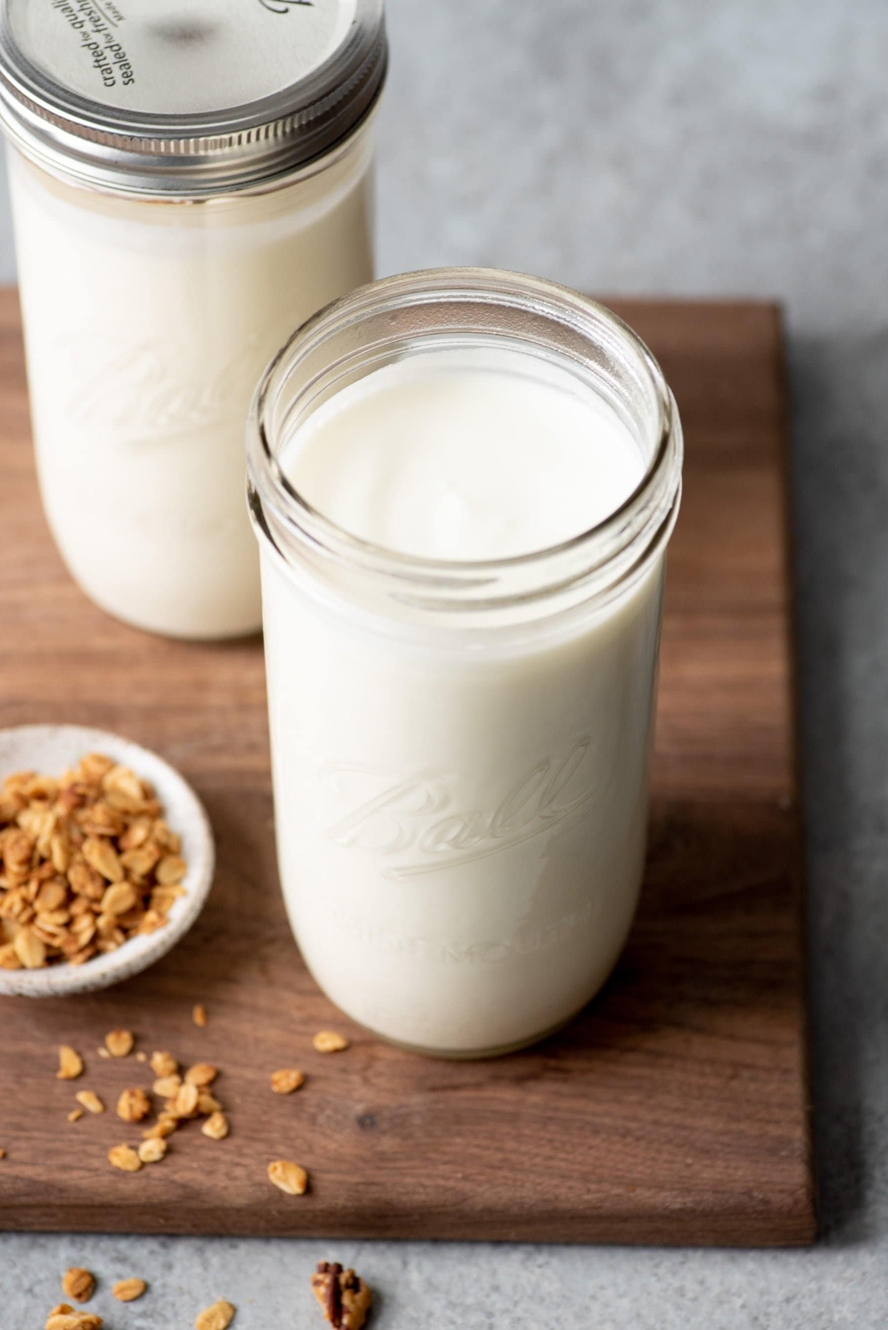 Tall glass jars filled with homemade yogurt, on a dark wooden cutting board