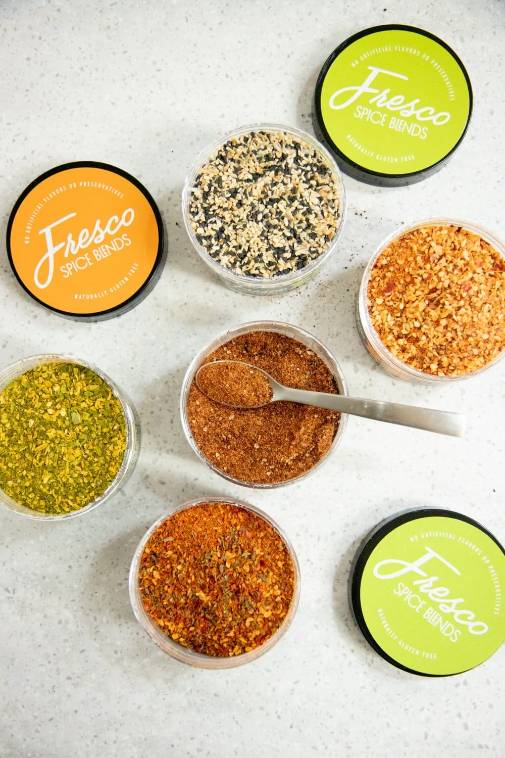 Overhead shot of open Fresco Spice Blends containers, with their lids nearby