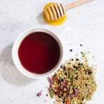 """Overhead shot of tea in a white teacup, with herbs and a honey dipper nearby. Text overlay reads """"Immune Boon Herbal Tea."""""""