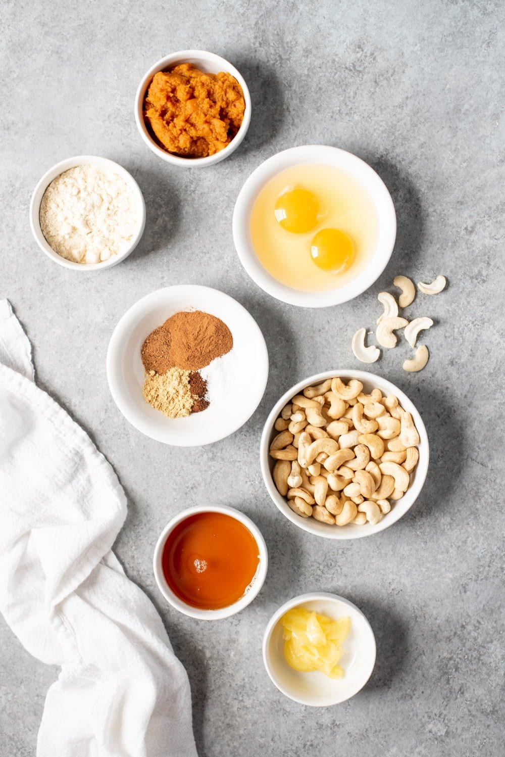 Ingredients for Grain-Free Pumpkin Bread in individual white bowls - pumpkin, cashews, spices, eggs, coconut flour