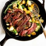 Overhead shot of potatoes and Brussels sprouts in a cast iron skillet, topped with a sliced seared steak