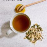 """Overhead shot of tea in a white teacup, with herbs and a honey dipper nearby. Text overlay reads """"Sore Throat Antidote Herbal Tea."""""""