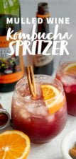 Mulled Wine Kombucha Spritzer in clear glasses with orange slices and a cinnamon stick floating on top, with the ingredients for the drink behind the glasses. Text overlay lists the name of the drink.
