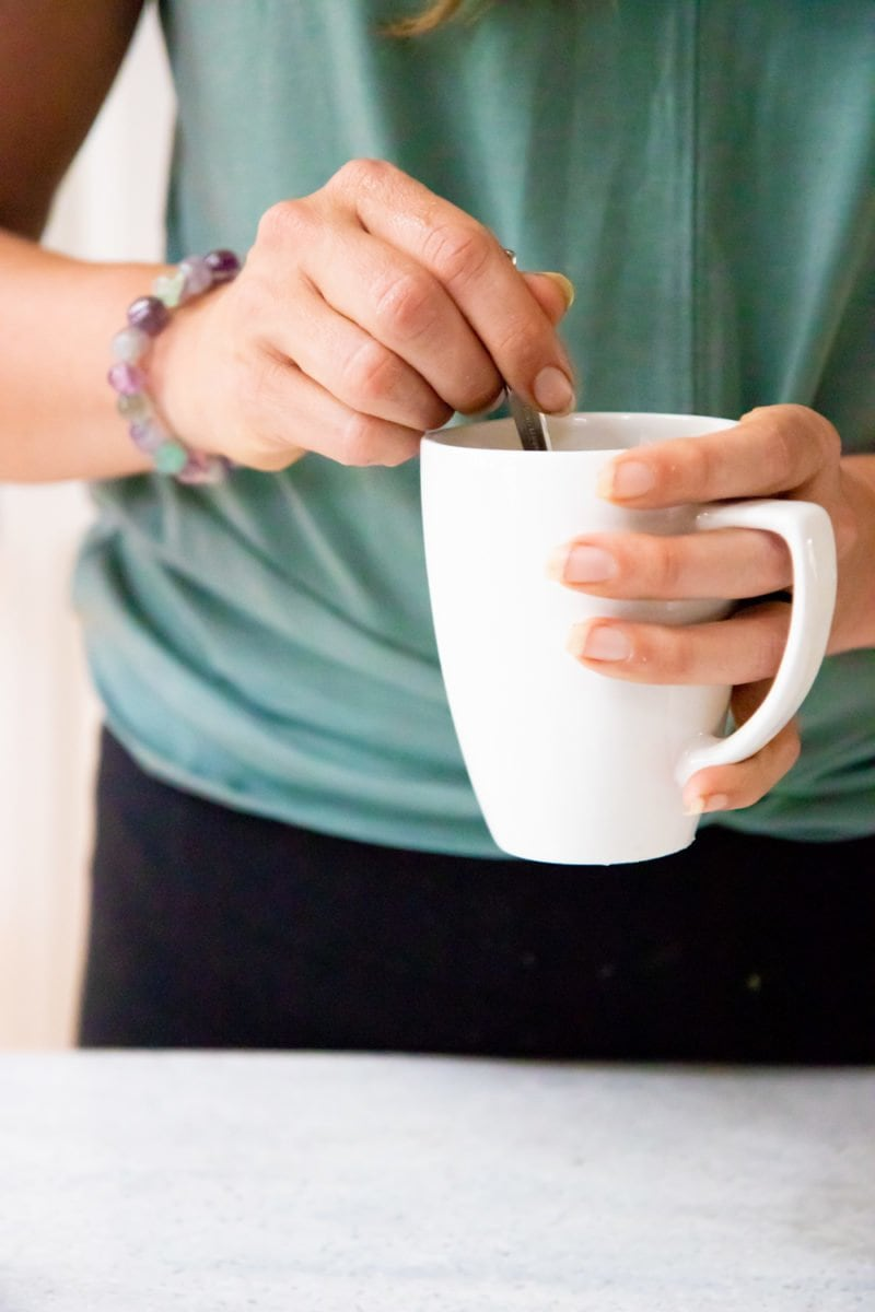 Hands holding a white mug and a spoon. The person is wearing a green shirt and a bracelet.