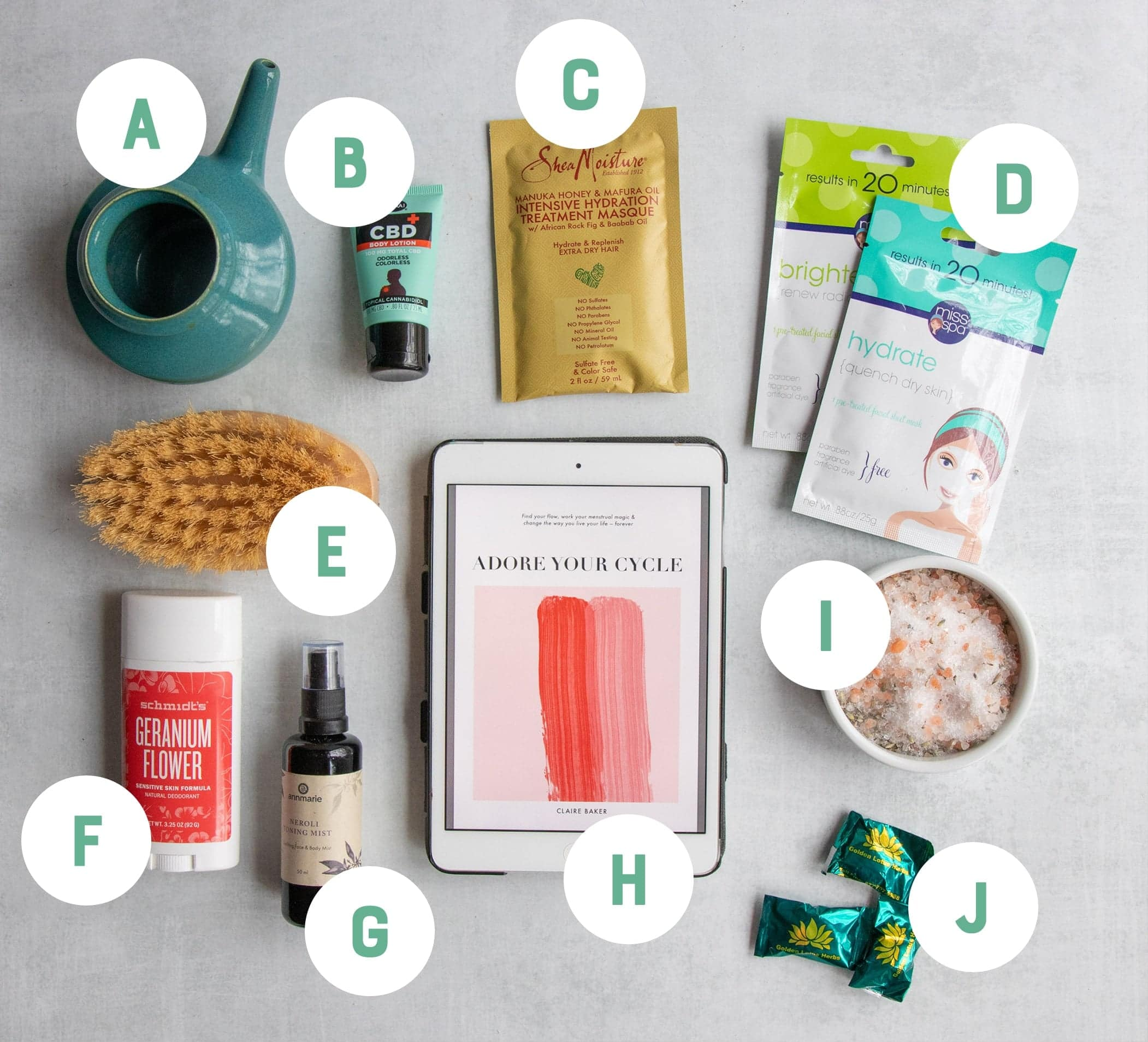 Natural health items arranged on a gray backdrop and labeled with letters: a ceramic neti pot, natural deodorant, face and hair masks, a dry brush, an ebook, bath salts