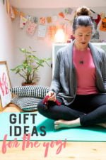 "Woman sitting cross-legged on a blue yoga mat. Text overlay reads ""Gift Ideas for the Yogi."""