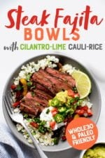 "Steak Fajita Bowls with Cilantro-Lime Cauliflower Rice in a grey bowl on a white background, with toppings in individual bowls nearby. A text overlay reads ""Steak Fajita Bowls with Cilantro-Lime Cauli-Rice. Whole30 and Paleo Friendly."""
