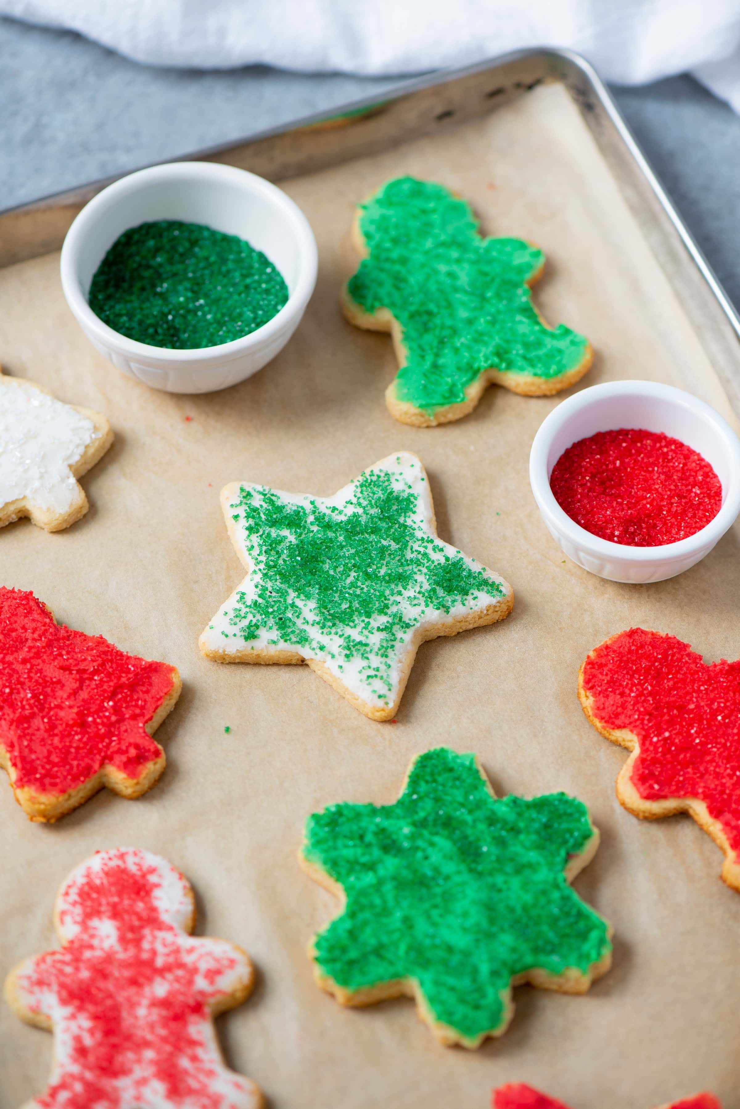 Grain-Free Paleo Cut-Out Sugar Cookies on parchment paper, topped with frosting and sprinkles