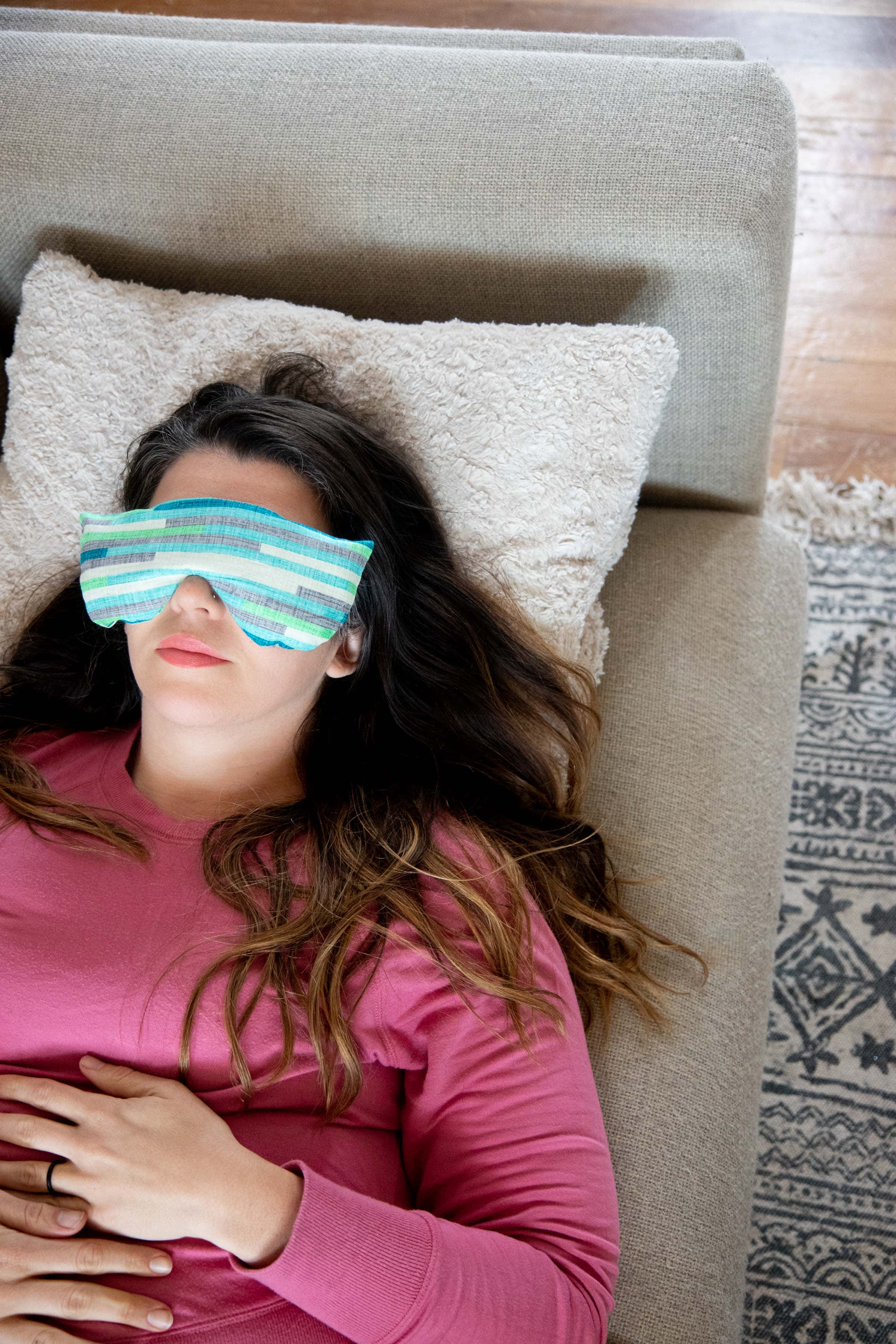 Brunette woman in a pink shirt lying on a grey couch with a Soothing Headache Eye Masks over her eyes