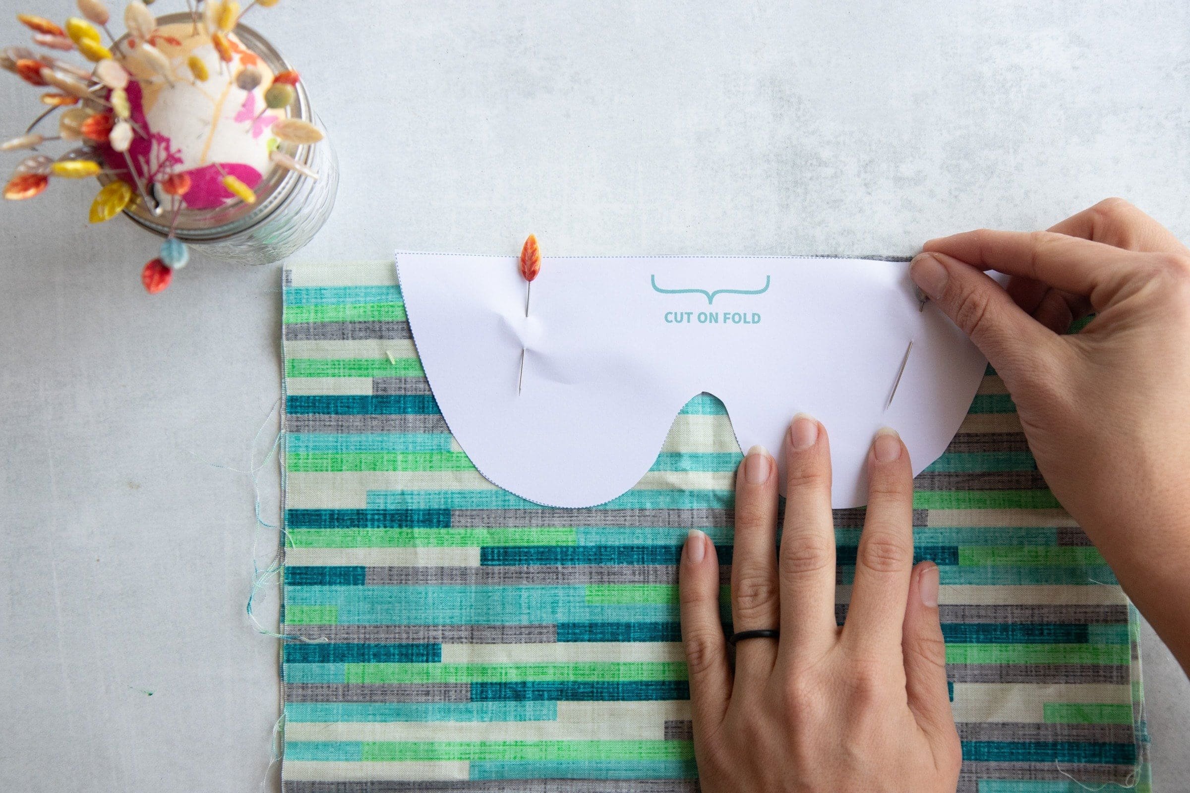 Hands pinning a paper pattern for Soothing Headache Eye Masks to striped fabric