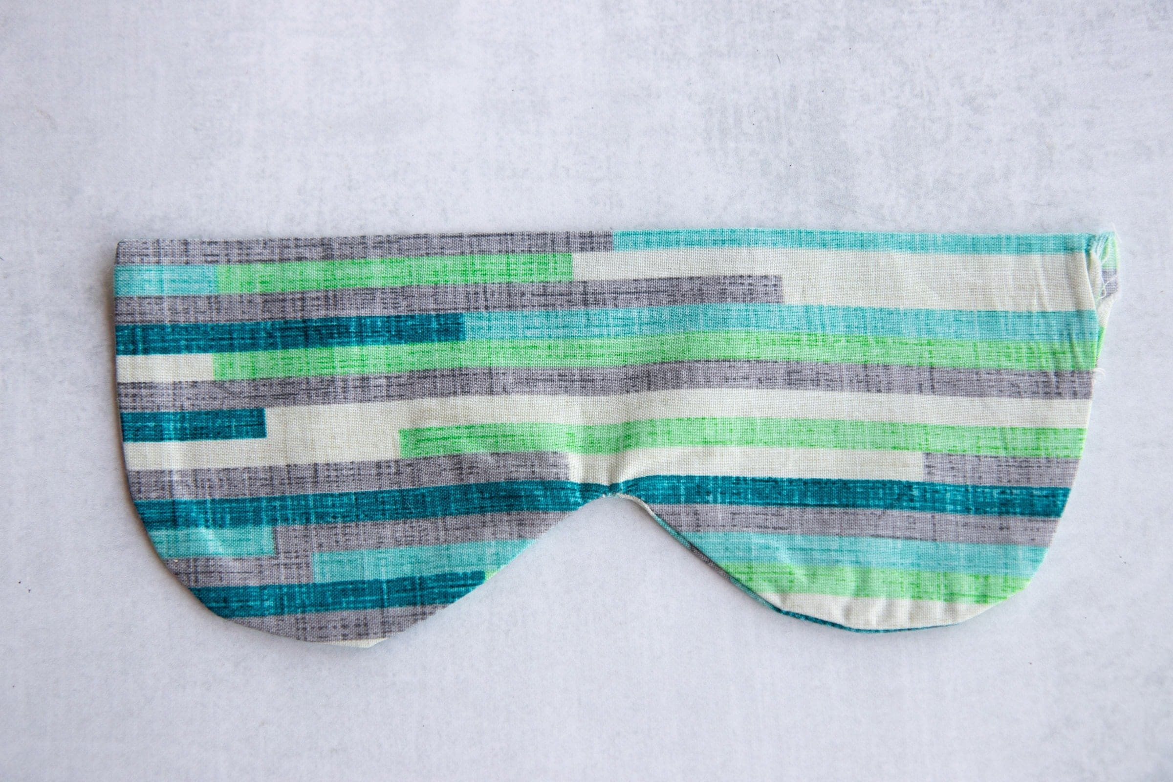 Blue, green, white, and grey Soothing Headache Eye Masks sewn together but unfilled