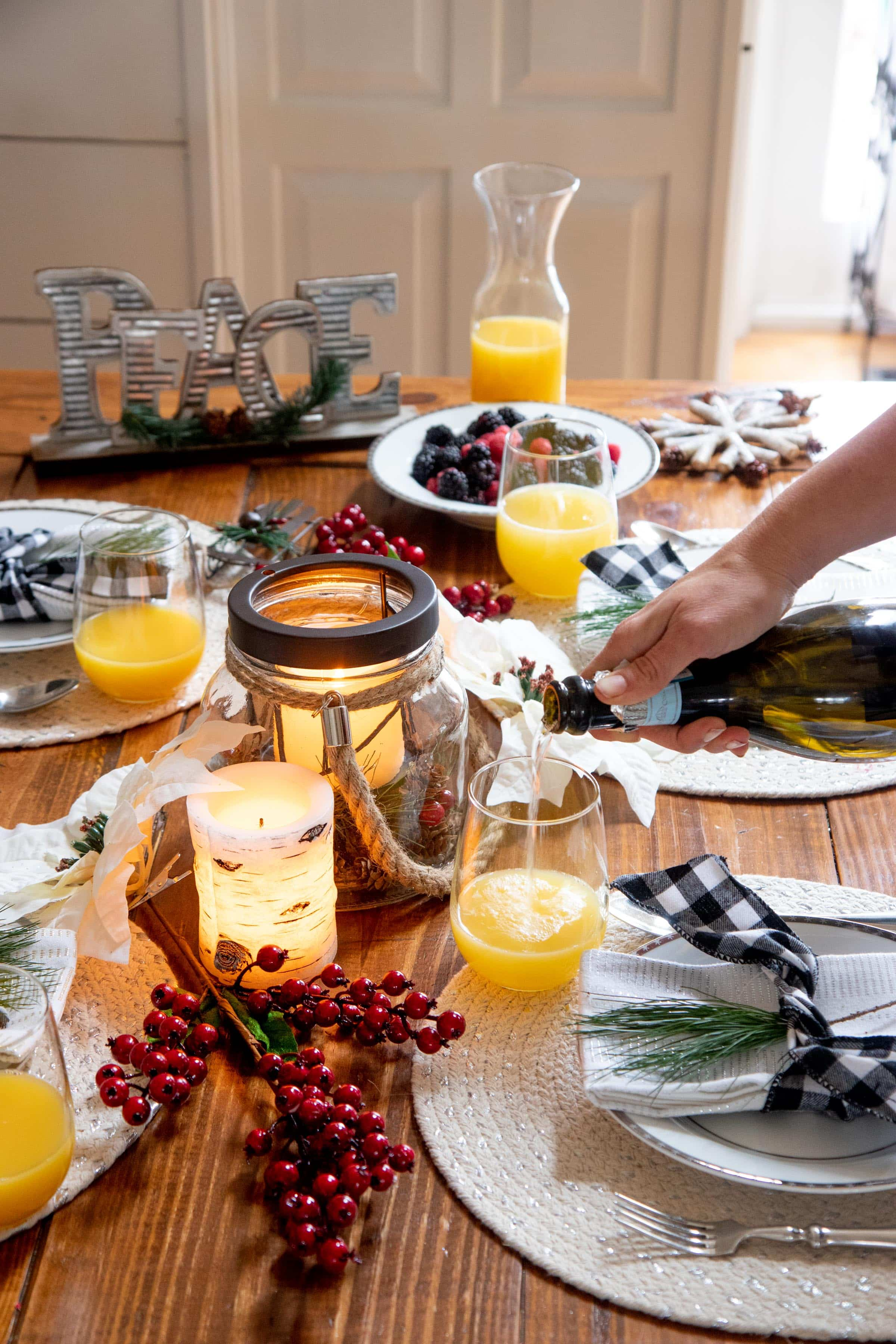 Hand pouring mimosas into glasses on a table set for the holidays.