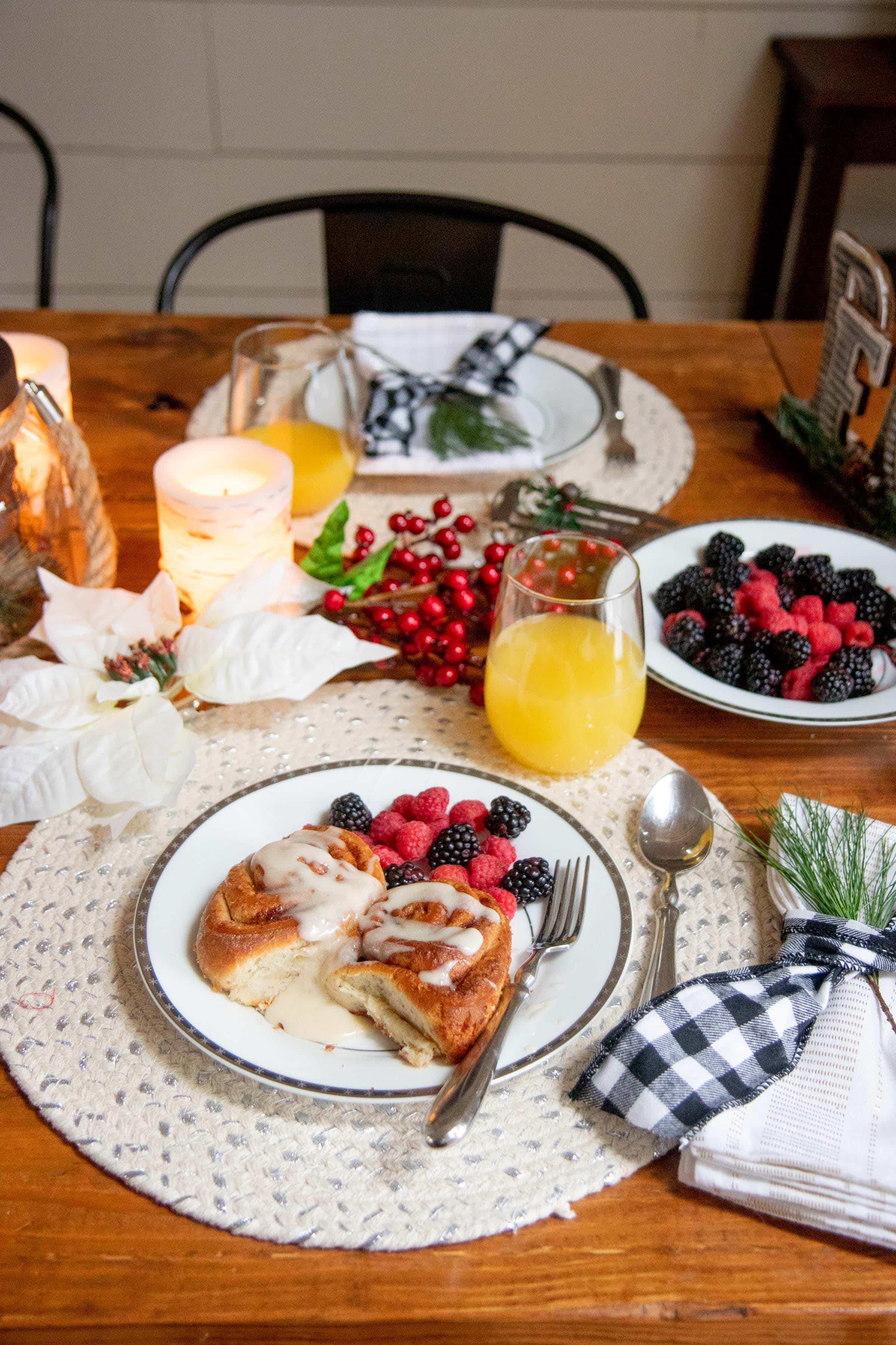 A plated Christmas breakfast, with cinnamon rolls and berries on a white plate, with a mimosa and more place settings behind.