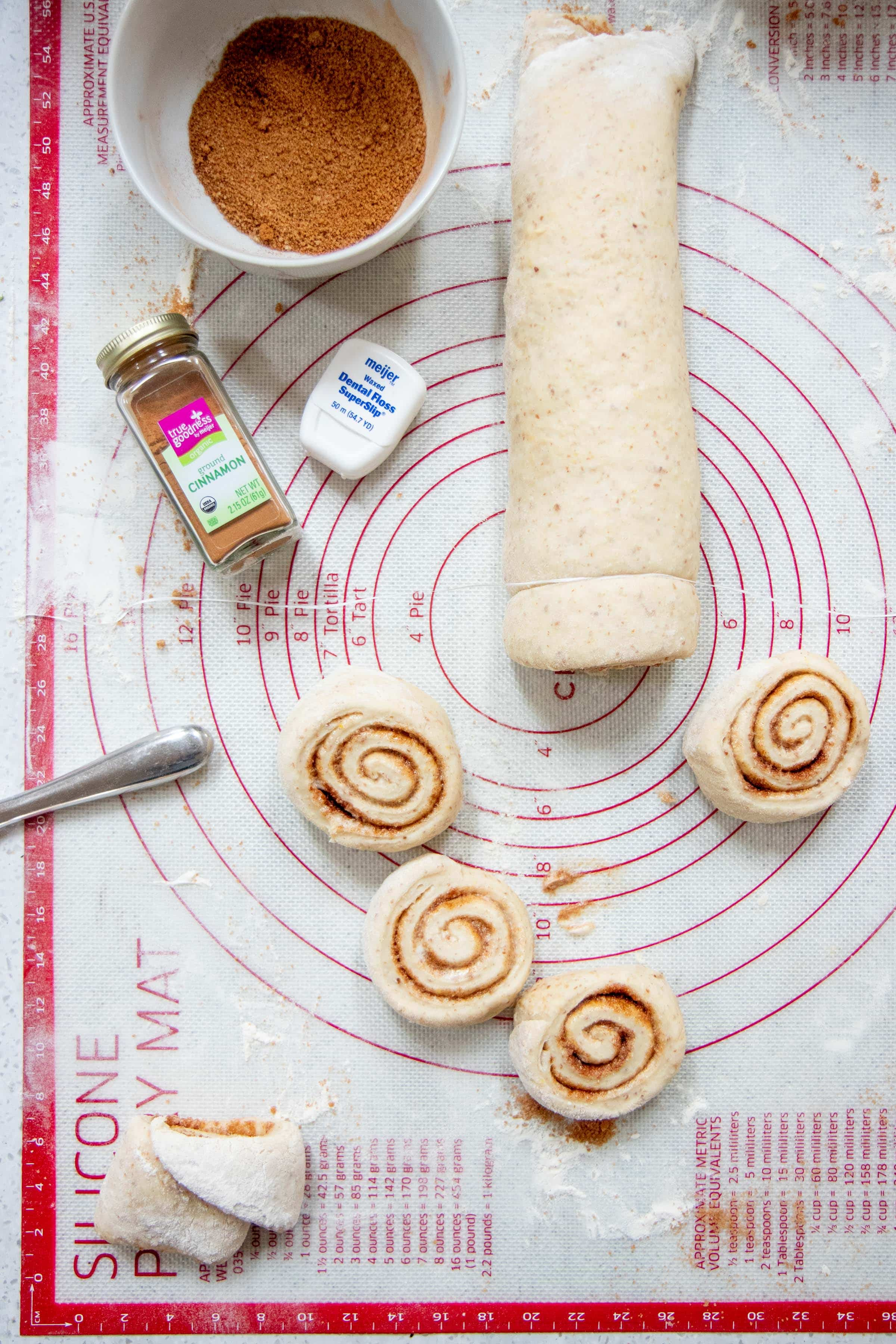 Vegan Cinnamon Rolls being sliced with dental floss, with some already cut rolls nearby