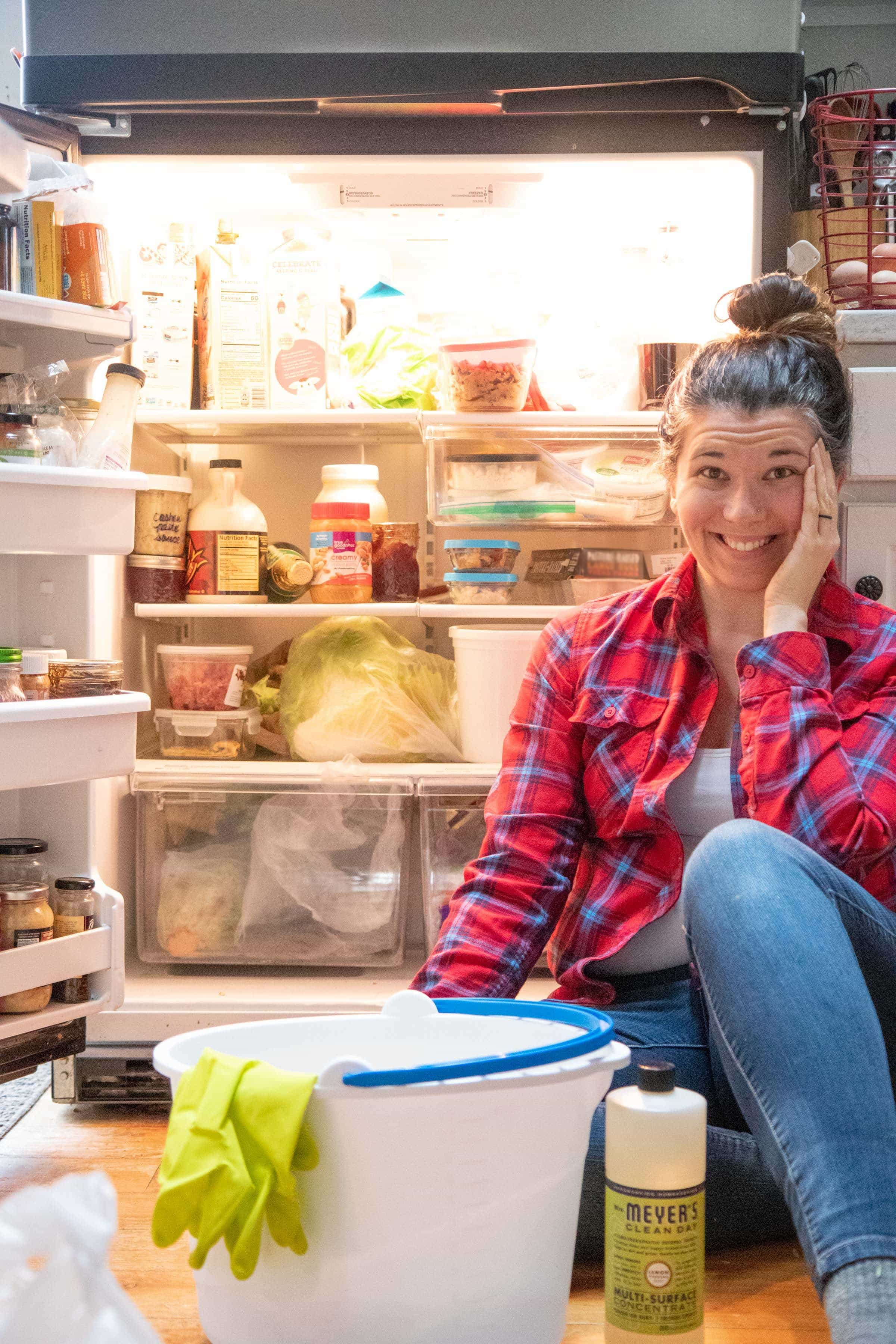 Brunette woman sitting in front of an open fridge with a mop bucket and bottle of cleaner