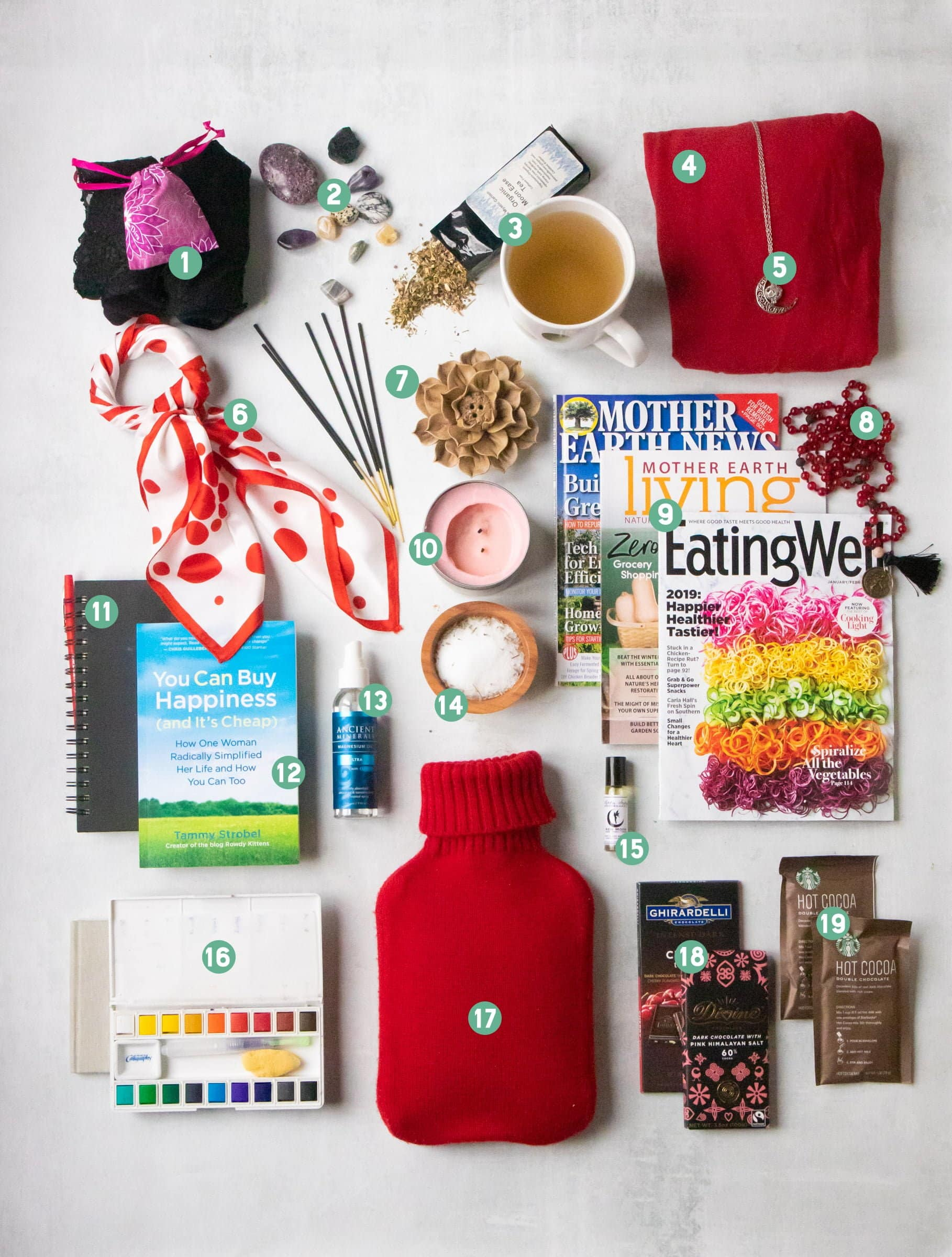 All the contents of a bleed box laid out and numbered - a menstrual cup, tea, crystals, a mala, magazines, art supplies, chocolate, a hot water bottle, a scarf, incense, and more.