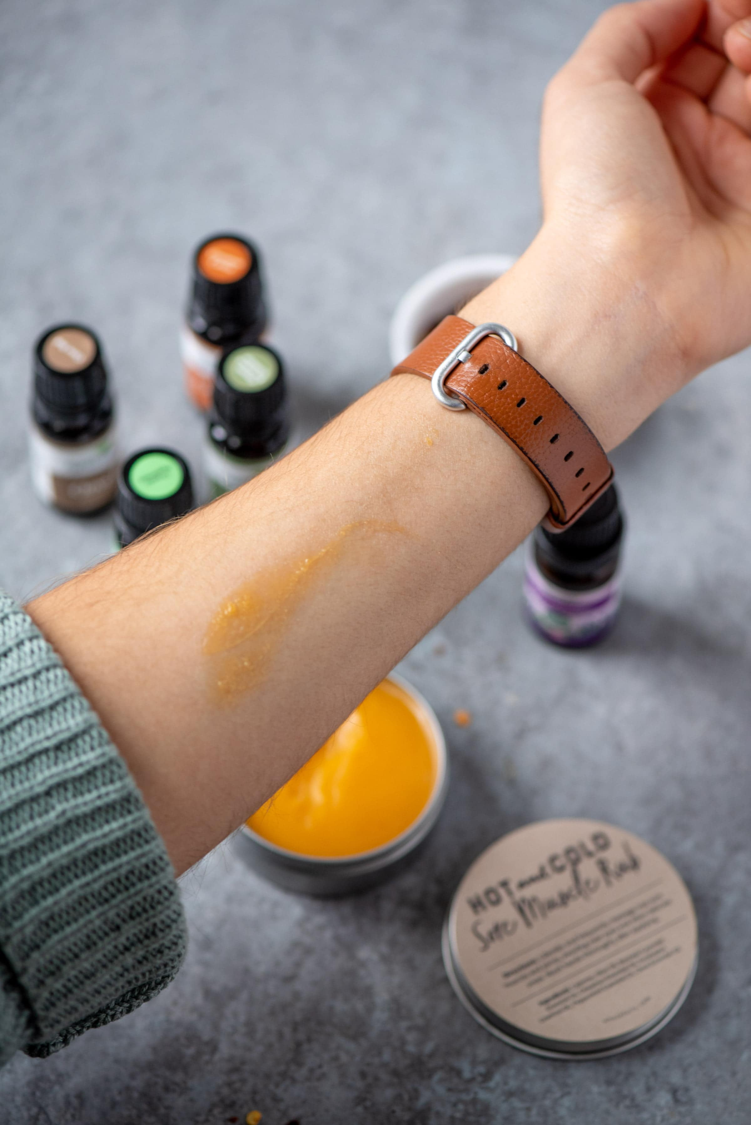 DIY Hot and Cold Sore Muscle Rub spread on a woman's forearm. The tin of balm and bottles of essential oils are in the background.