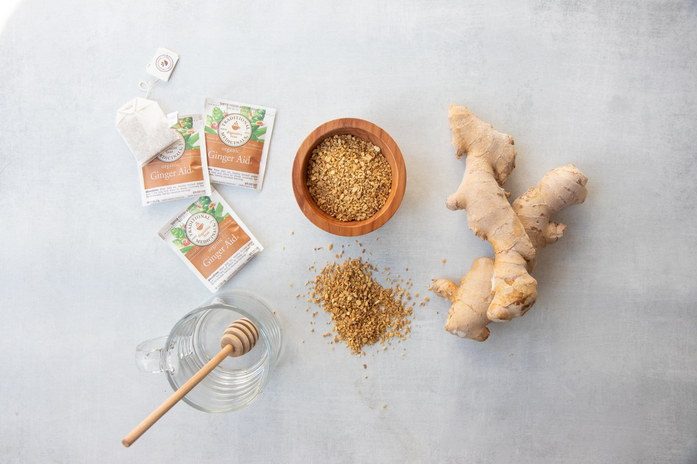 Three ways to make ginger tea on a grey background - bagged tea, dried ginger root, and fresh ginger root