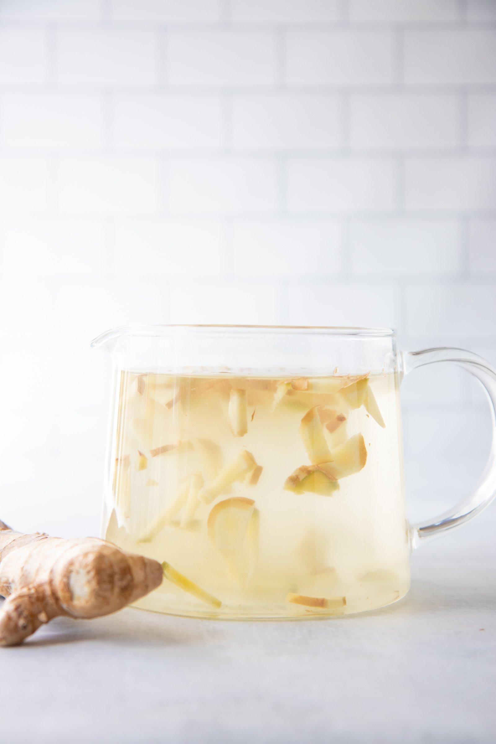 Glass tea pot full of ginger tea made with fresh ginger root