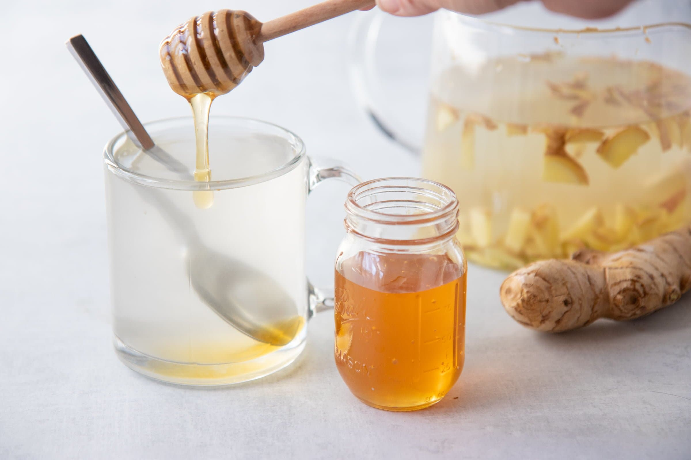 Honey stirrer drizzling honey into a clear mug of ginger tea