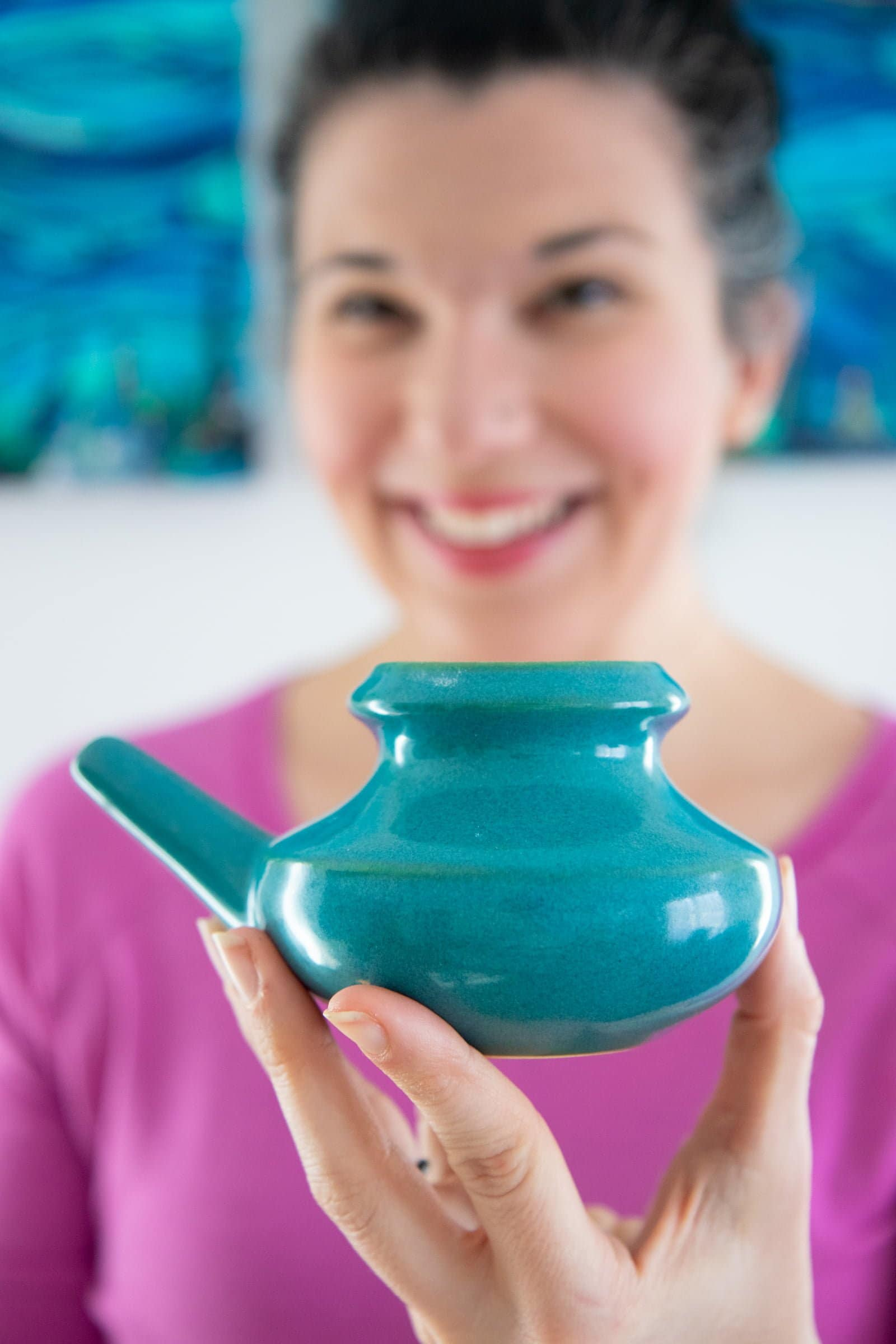 Woman in a pink shirt holding a ceramic neti pot in front of her and smiling