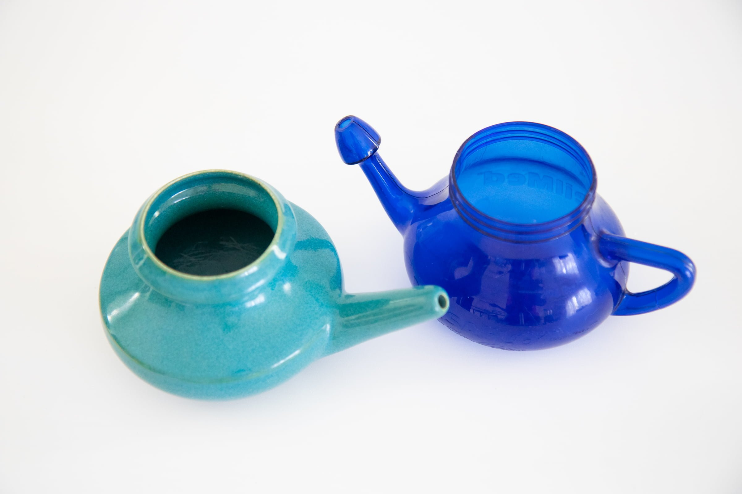 Ceramic neti pot next to a blue plastic neti pot.
