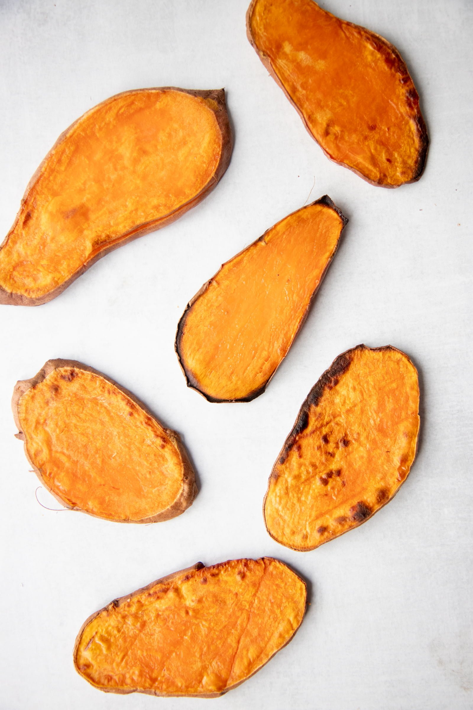Sweet potato planks toasted and laid out on a white background
