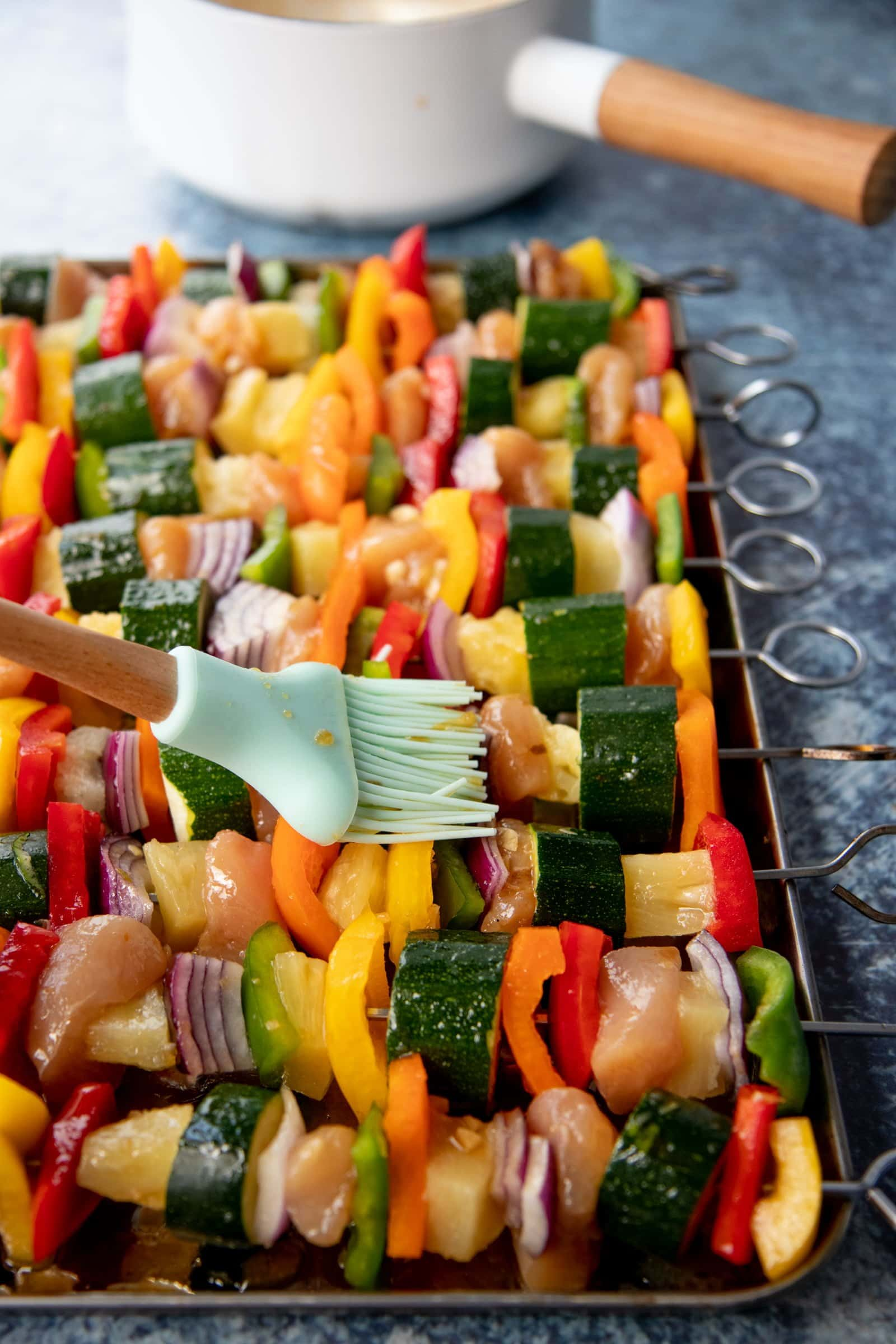Pastry brush brushing marinade onto a tray of metal skewers threaded with chicken, vegetables, and pineapple to make Grilled Chicken Kabobs