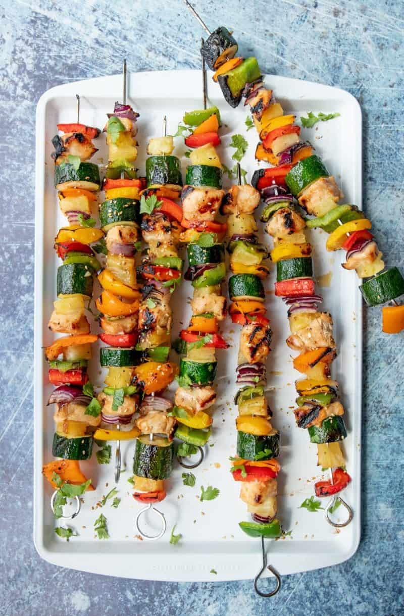 A white platter full of Grilled Hawaiian Chicken Kabobs on metal skewers