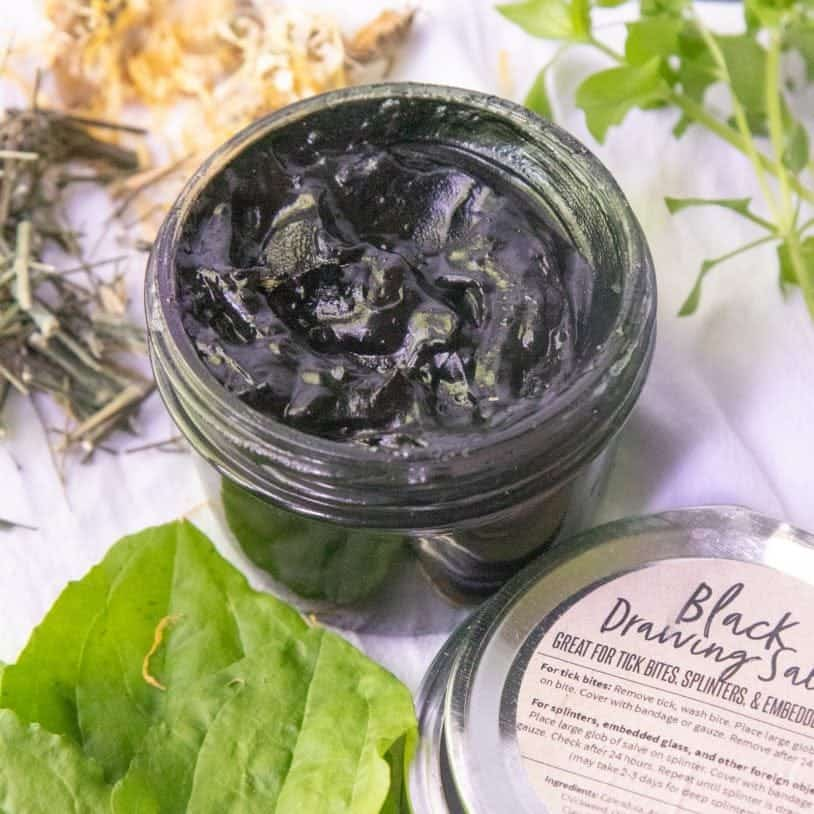 A glass jar of black drawing salve with herbs surrounding it, and a labeled lid next to it.