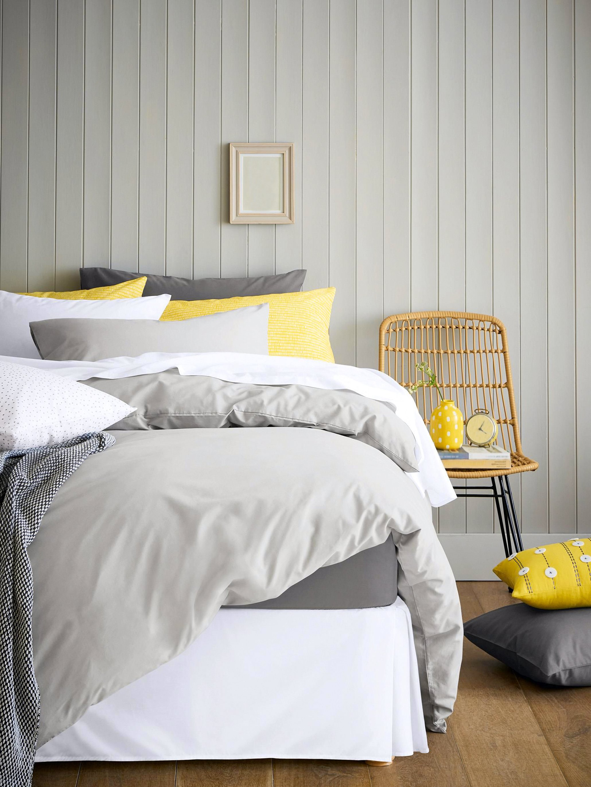 Bed with a grey comforter and white, grey, and yellow pillows. Story describes what to do when you can't fall asleep.