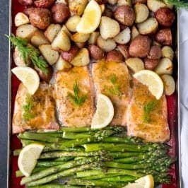 Sheet pan covered with a silicon baking sheet, salmon, asparagus, potatoes, lemon slices, and herbs.